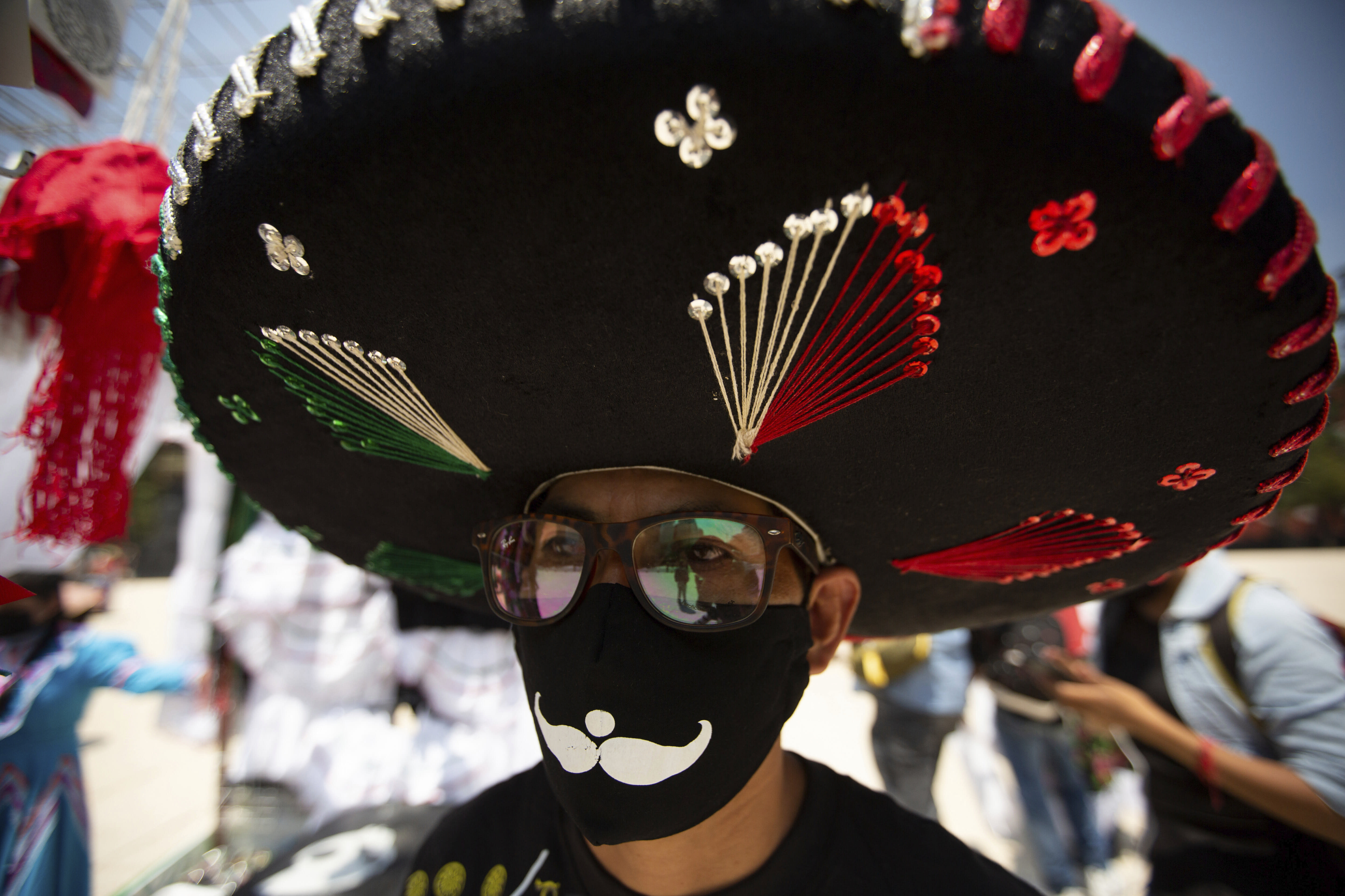 A souvenir vendor wearing a Mexican Charro hat and a mask to curb the spread of the new coronavirus pushes his cart to a new location after authorities allowed the selling of patriotic souvenirs for the upcoming independence day celebration, far from the city's downtown area as a precaution against the spread of COVID-19 in Mexico City, Wednesday, Sept. 2, 2020. (AP Photo/Fernando Llano)