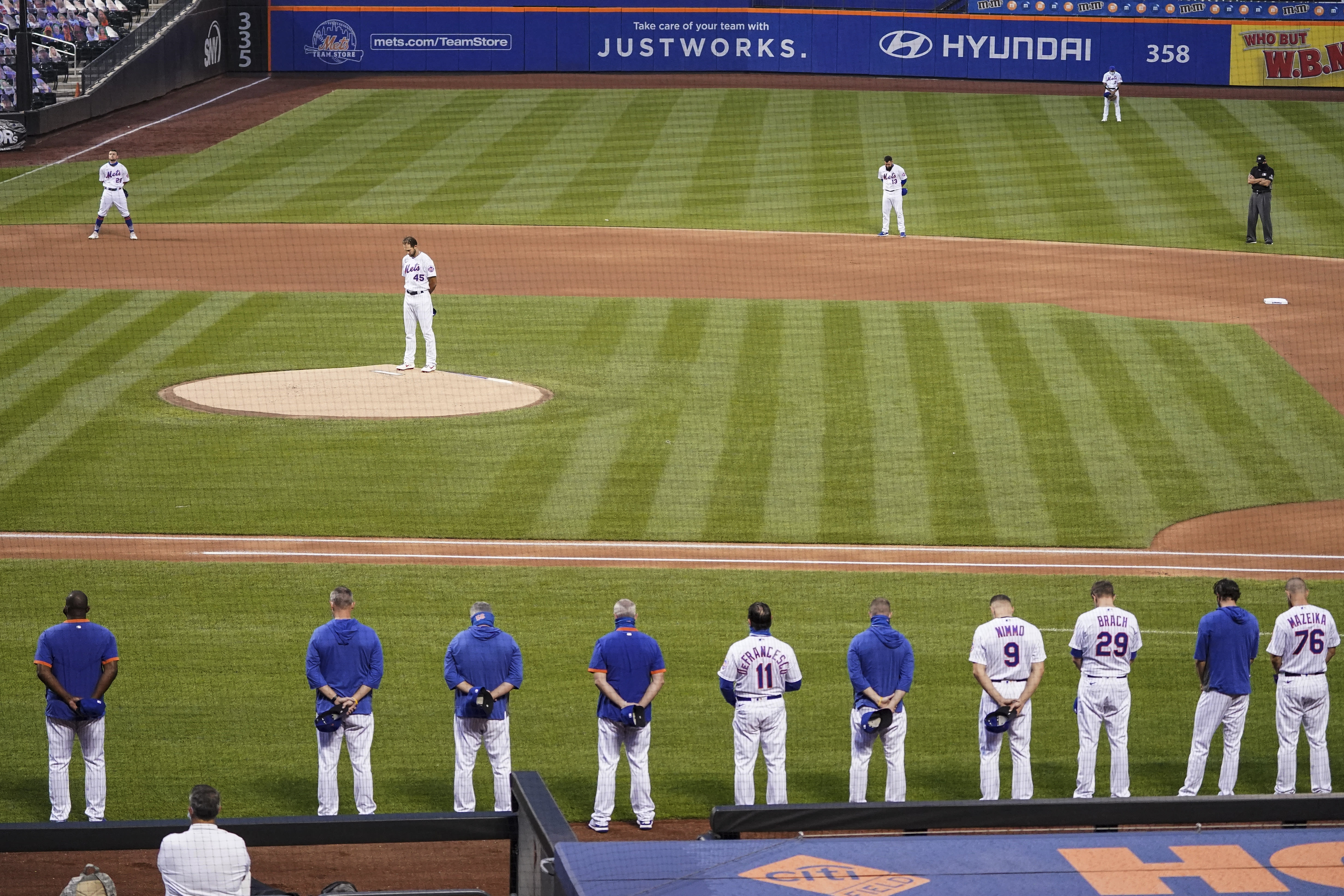 The New York Mets and Miami Marlins stand on the field and bow their heads before a scheduled baseball game Thursday, Aug. 27, 2020, in New York. Mets outfielder Dominic Smith — a Black man who wept Wednesday night discussing the shooting by police of a Black man in Wisconsin over the weekend — led New York onto the field. Players took their positions, then reserves and coaches filed out of both dugouts and stood silently for 42 seconds. Both teams then left the field, leaving only the black T-shirt at home. (AP Photo/John Minchillo)