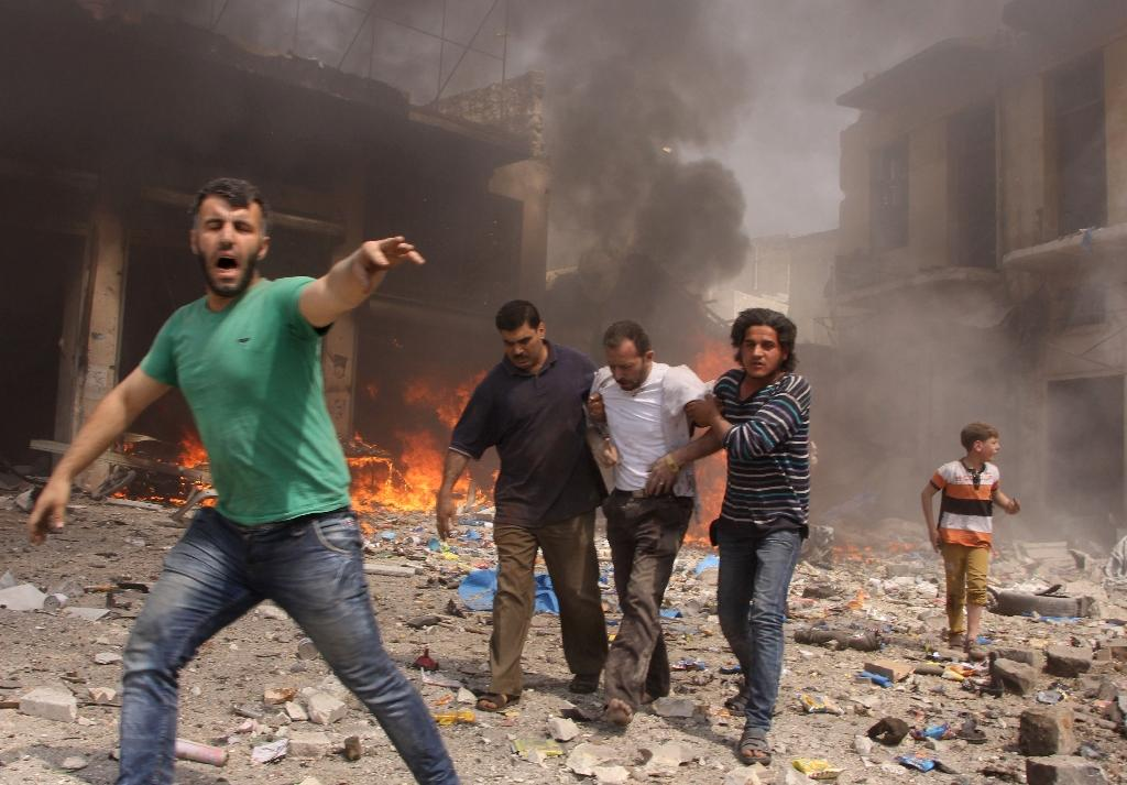 Syrian men react and help the inured following a reported barrel bomb attack by Syrian government forces that hit an open market in the northern city of Aleppo, on June 3, 2015, killing and injuring people