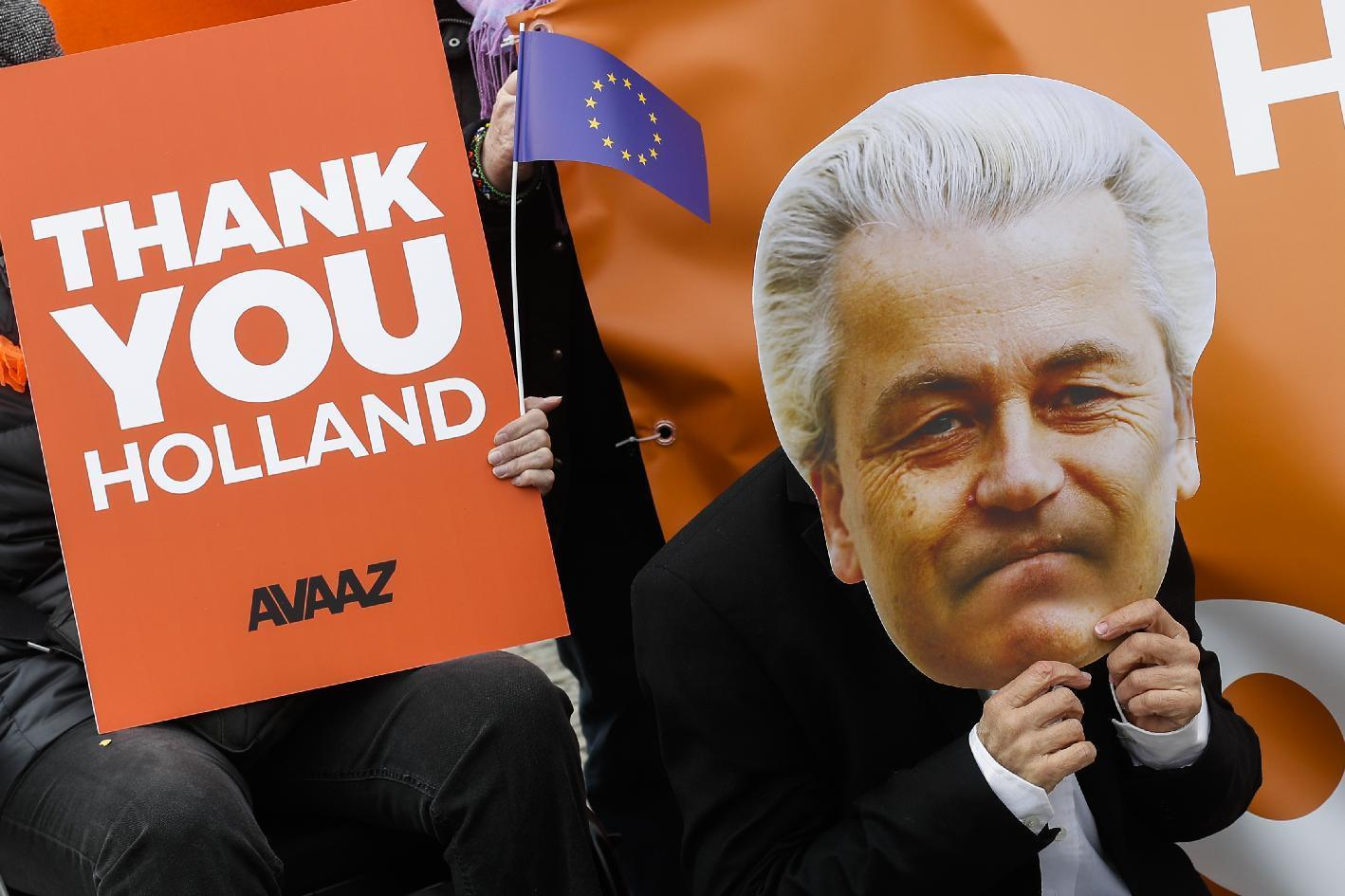 An activist of the AVAAZ network with a mask of Dutch anti-Islam lawmaker Geert Wilders attends an event to celebrate the election results in the Netherlands in front of the Brandenburg Gate in Berlin, Thursday, March 16, 2017. (AP Photo/Markus Schreiber)