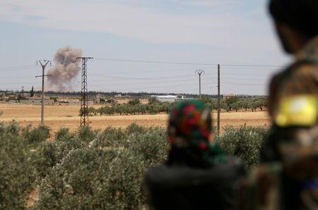 Fighters of the Syria Democratic Forces (SDF) look at a smoke rising from what they say were U.S.-led air strikes on positions controlled by Islamic State militants, in the western rural area of Manbij, in Aleppo Governorate, Syria June 11, 2016. REUTERS/Rodi Said