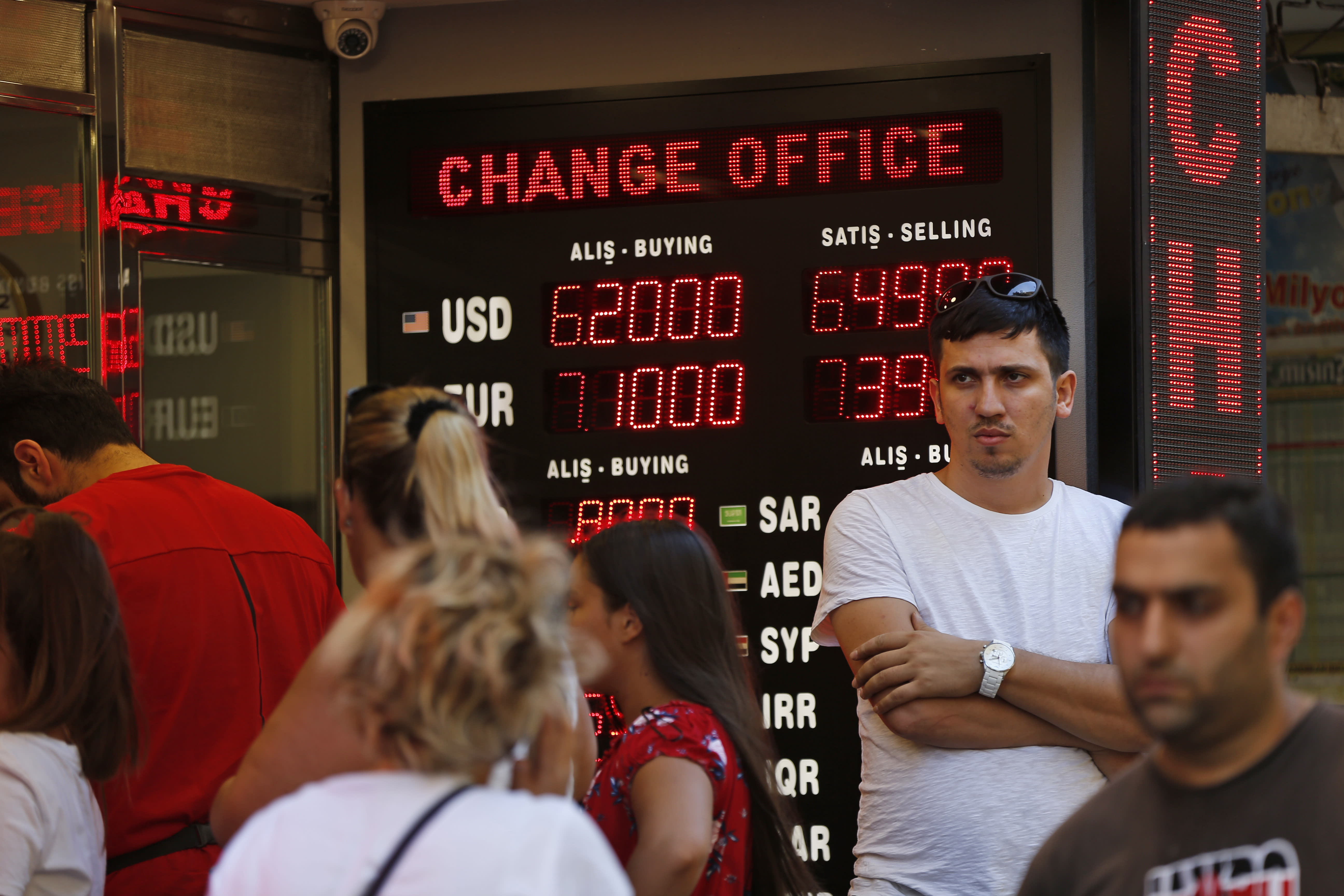 FILE- In this Tuesday, Aug. 14, 2018, file photo people line up at a currency exchange shop in Istanbul. Investors have been pulling out of Turkey's markets, sending its stock market and currency plunging. That's making debt that Turkish companies owe in dollar terms even more expensive to pay back, which only further weakens the country's financial system. (AP Photo/Lefteris Pitarakis, File)