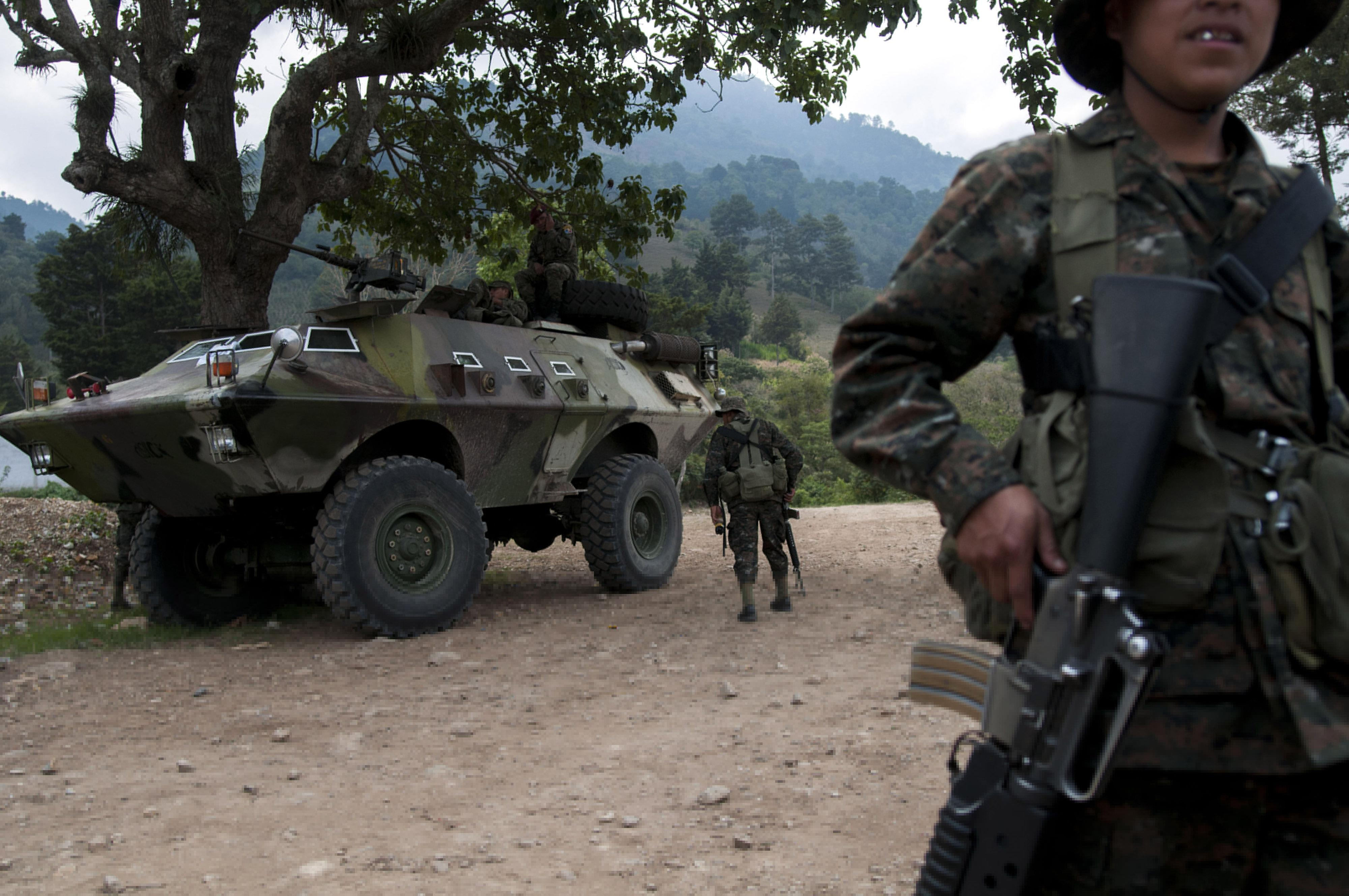 Soldiers patrol in San Rafael Las Flores, Guatemala, Thursday, May 2, 2013. Guatemala's government declared a state of emergency and banned public gatherings Thursday in four townships east of the capital following several days of violent clashes between police and anti-mining protesters. The government sent in 500 police officers and 2,000 soldiers, some in armored personnel vehicles. It said protesters were armed with guns and explosives. Clashes have involved police, mine security guards and local protesters. (AP Photo/Luis Soto)