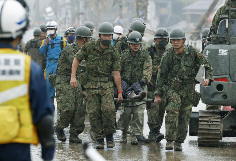 Japanese Self-Defence Force soldiers carry rescured person using a stretcher at a flooding site caused by a heavy rain in Kuma village