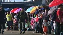 Typhoon survivors try to flee, as others return to devastated villages