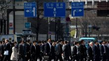 Bank of Japan trims inflation view, stands pat on policy