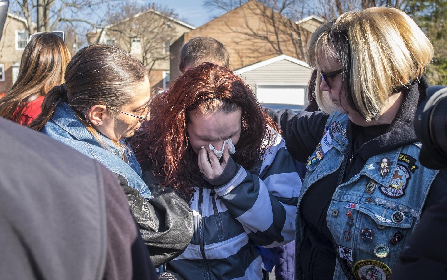Rose Hunsicker, center, the biological mother of Grace Packer, weeps as she prays with members of Bikers Against Child Abuse outside the church Monday, Jan. 16, 2017, on her way in to a memorial service for Packer, the local teen who who authorities say was killed and dismembered by her adoptive mother and her boyfriend, at the New Life Presbyterian Church in Glenside, Pa. (Ed Hille/The Philadelphia Inquirer via AP)
