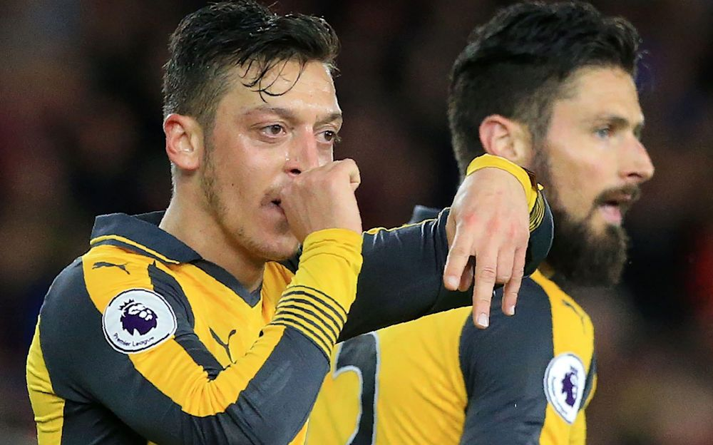 Rule of thumb: Mesut Ozil celebrates his goal, Olivier Giroud celebrates his luxuriant beard - AFP
