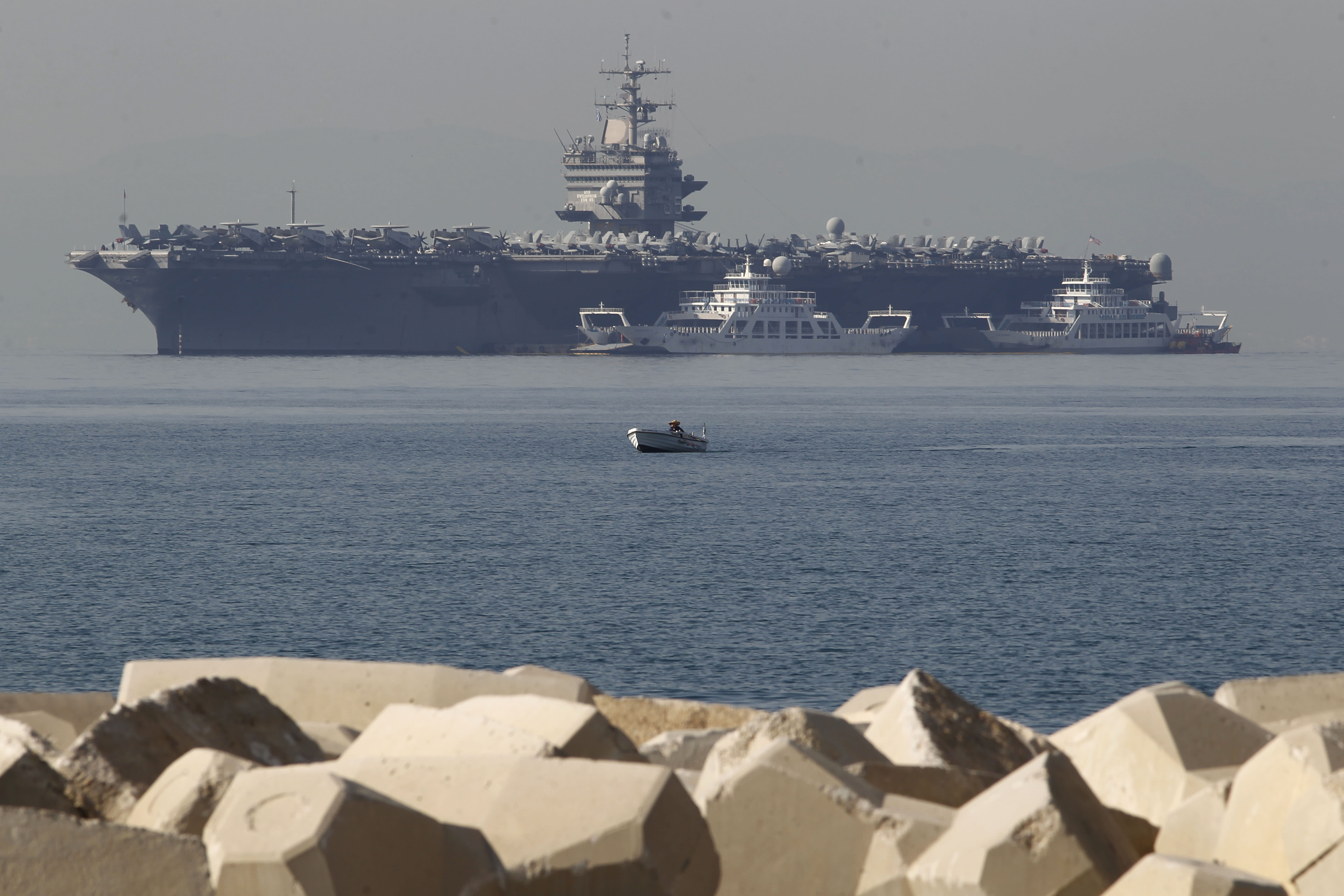FILE - In this Thursday, March 29, 2012 file photo, a small boat pass in front of the aircraft carrier USS Enterprise is seen anchored of the coast of Faliro, near Athens. The U.S. Navy said Monday, April 9, 2012 that it has deployed a second aircraft carrier to the Persian Gulf region amid rising tensions with Iran over its nuclear program. The deployment of the nuclear-powered USS Enterprise along the Abraham Lincoln carrier strike group marks only the fourth time in the past decade that the Navy has had two aircraft carriers operating at the same time in the Persian Gulf and the Arabian Sea, said Cmdr. Amy Derrick-Frost of the Bahrain-based 5th Fleet. (AP Photo/Petros Giannakouris, File)