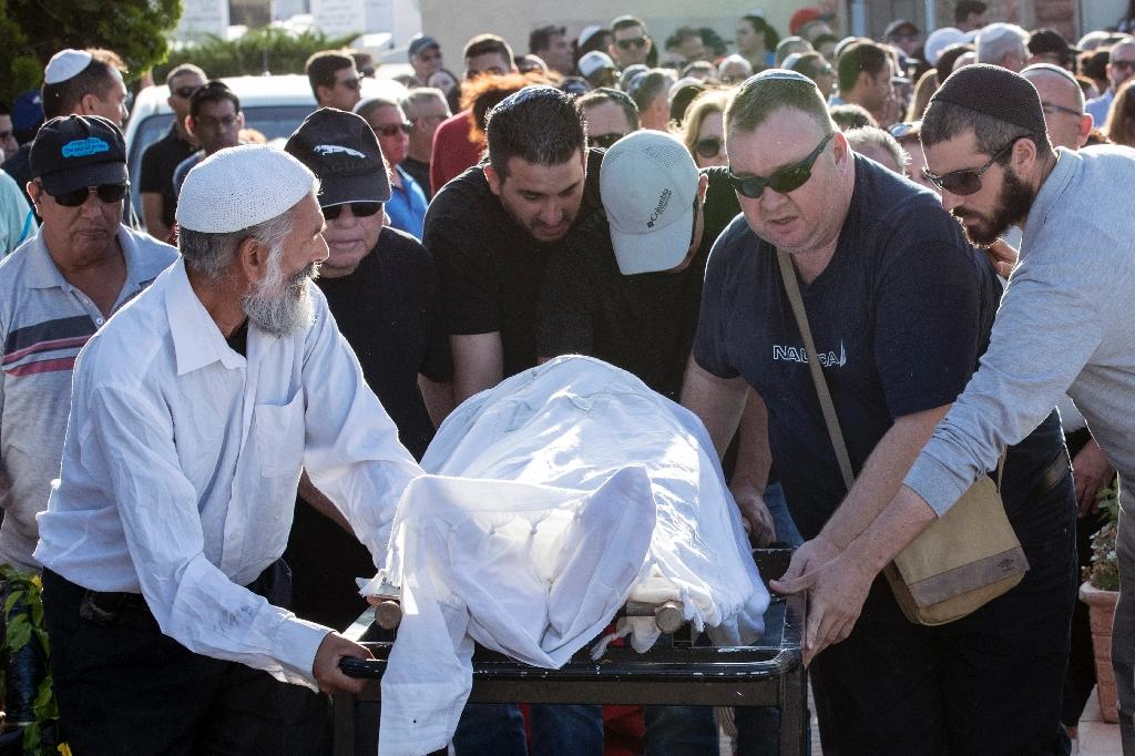 Friends and relatives of an Israeli victim of a shooting attack by two Palestinians in Tel Aviv carry his body on a stretcher during his funeral on June 9, 2016 (AFP Photo/Jack Guez)