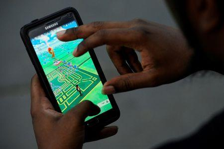 """A virtual map of Bryant Park is displayed on the screen as a man plays the augmented reality mobile game """"Pokemon Go"""" by Nintendo in New York City"""
