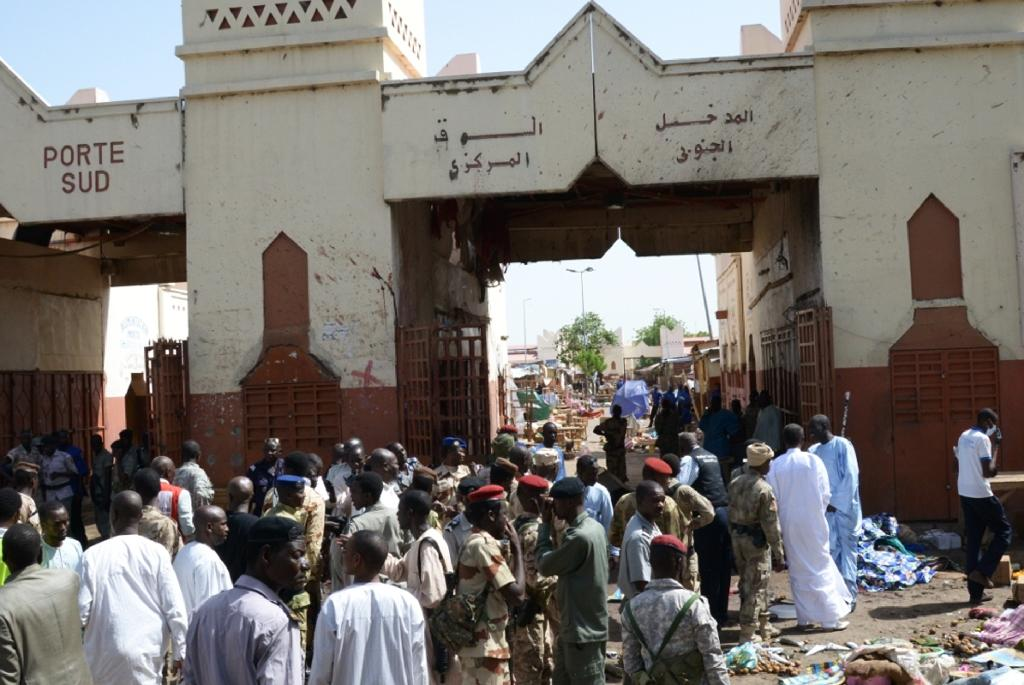 People and soldiers stand outside a market in N'Djamena following a suicide bomb attack on July 11, 2015 where at least 14 people were killed (AFP Photo/Brahim Adji)