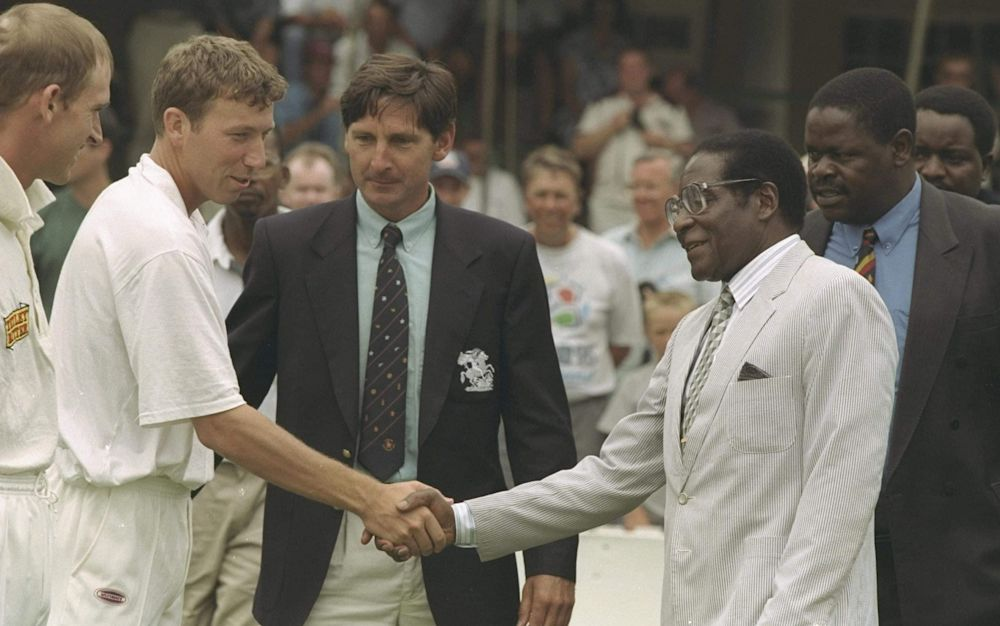 England captain Mike Atherton is presented to Zimbabwe's despotic president, Robert Mugabe - Getty Images