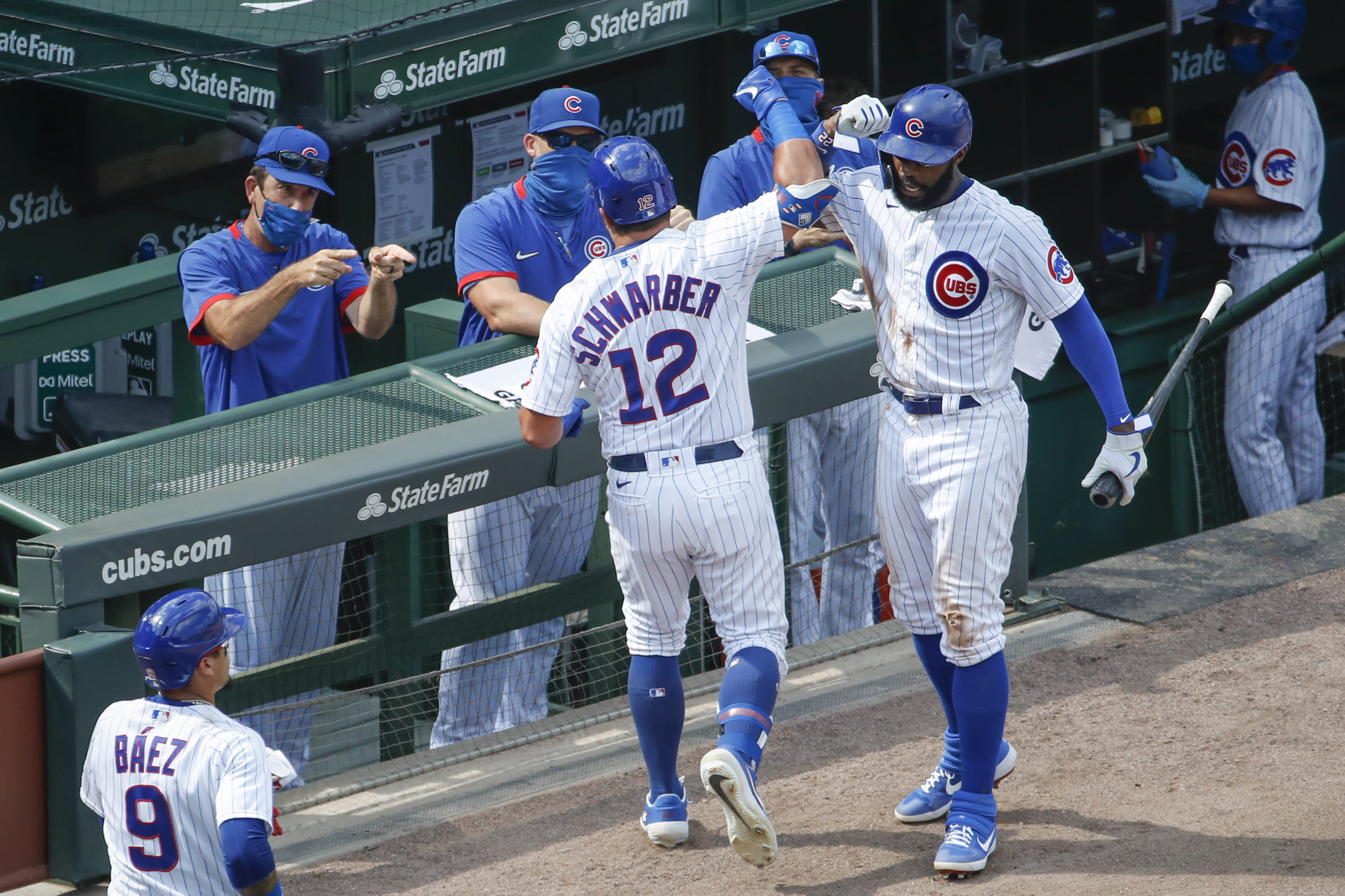 Chicago Cubs' Kyle Schwarber, center celebrates with Jason Heyward, right, after hitting a two-run home run against the Chicago White Sox during the sixth inning of a baseball game, Sunday, Aug. 23, 2020, in Chicago. (AP Photo/Kamil Krzaczynski)