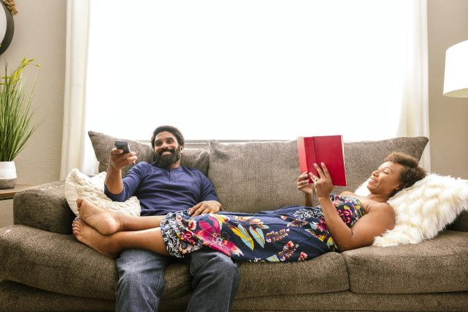 Husband watching television on the sofa with wife's feet resting on lap