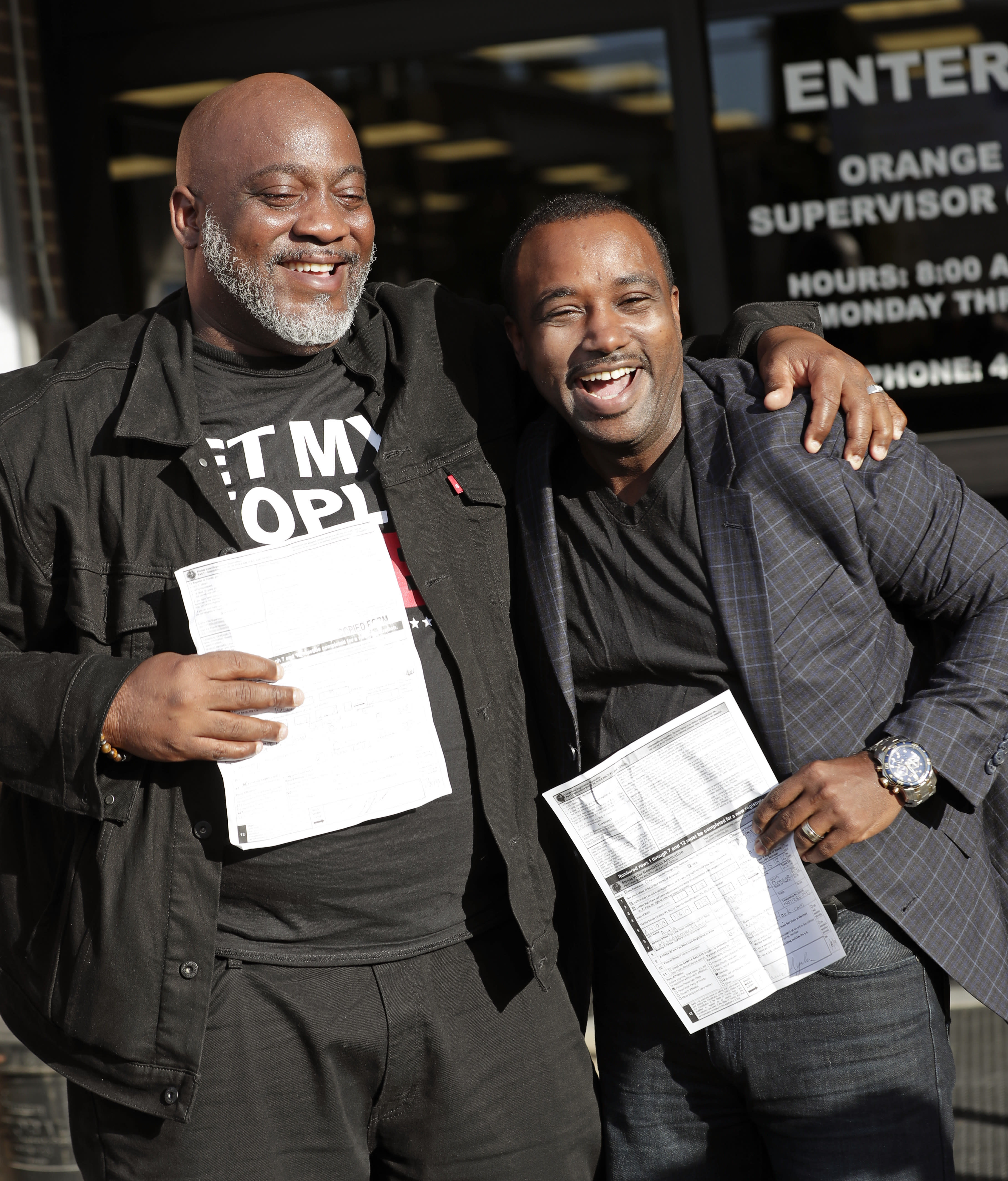 Former felons Desmond Meade, president of the Florida Rights Restoration Coalition, left, and David Ayala, husband of State Attorney Aramis Ayala, celebrate with copies of their voter registration forms after they registered at the Supervisor of Elections office Tuesday, Jan. 8, 2019, in Orlando, Fla. Former felons in Florida began registering for elections on Tuesday, when an amendment that restores their voting rights went into effect. (AP Photo/John Raoux)