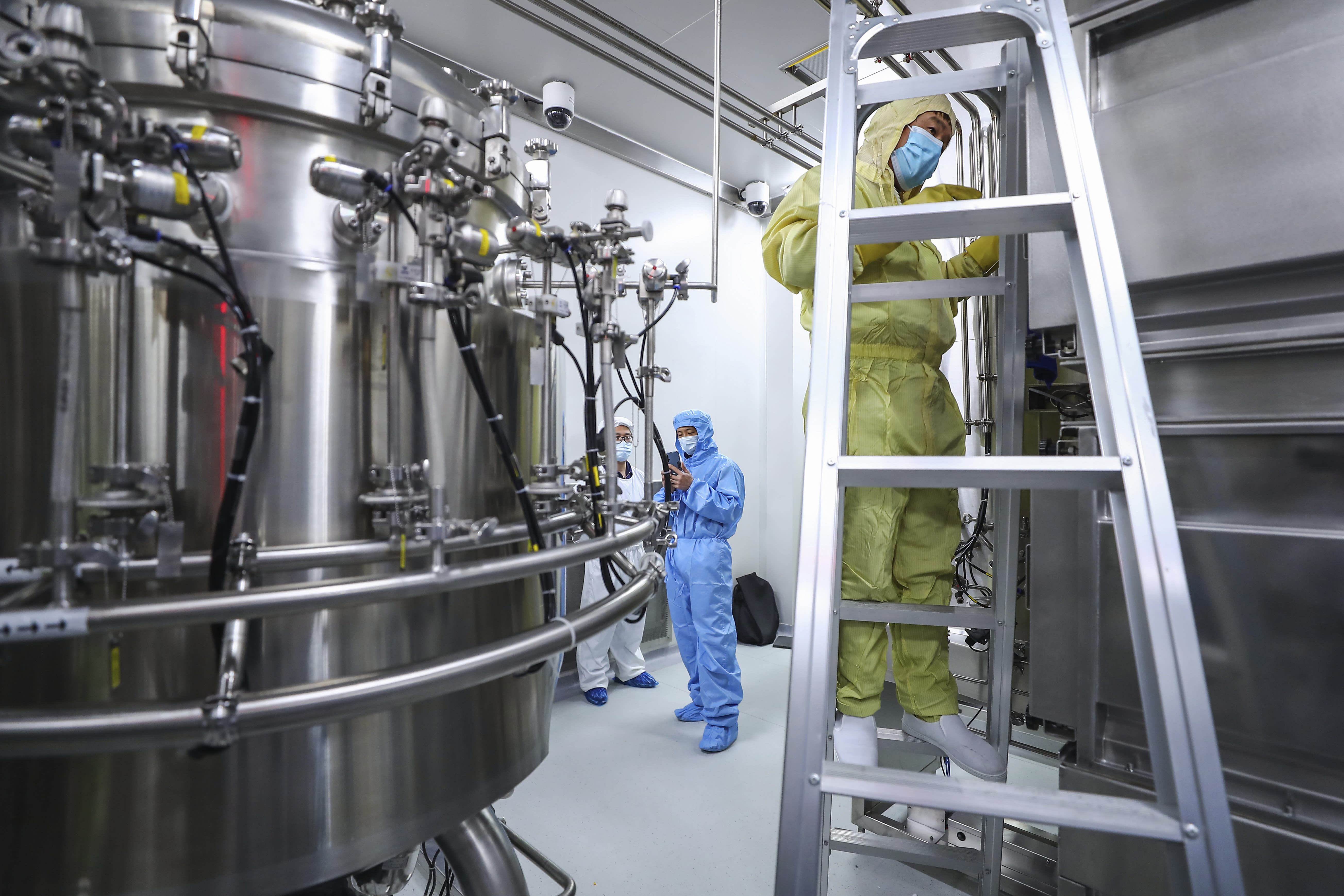 In this April 11, 2020, photo released by Xinhua News Agency, staff members check and clean equipments at a vaccine production plant of SinoPharm in Beijing. In the global race to make a coronavirus vaccine, the state-owned Chinese company is boasting that it gave its employees, including top executives, experimental shots even before the government OK'd testing in people. (Zhang Yuwei/Xinhua via AP)
