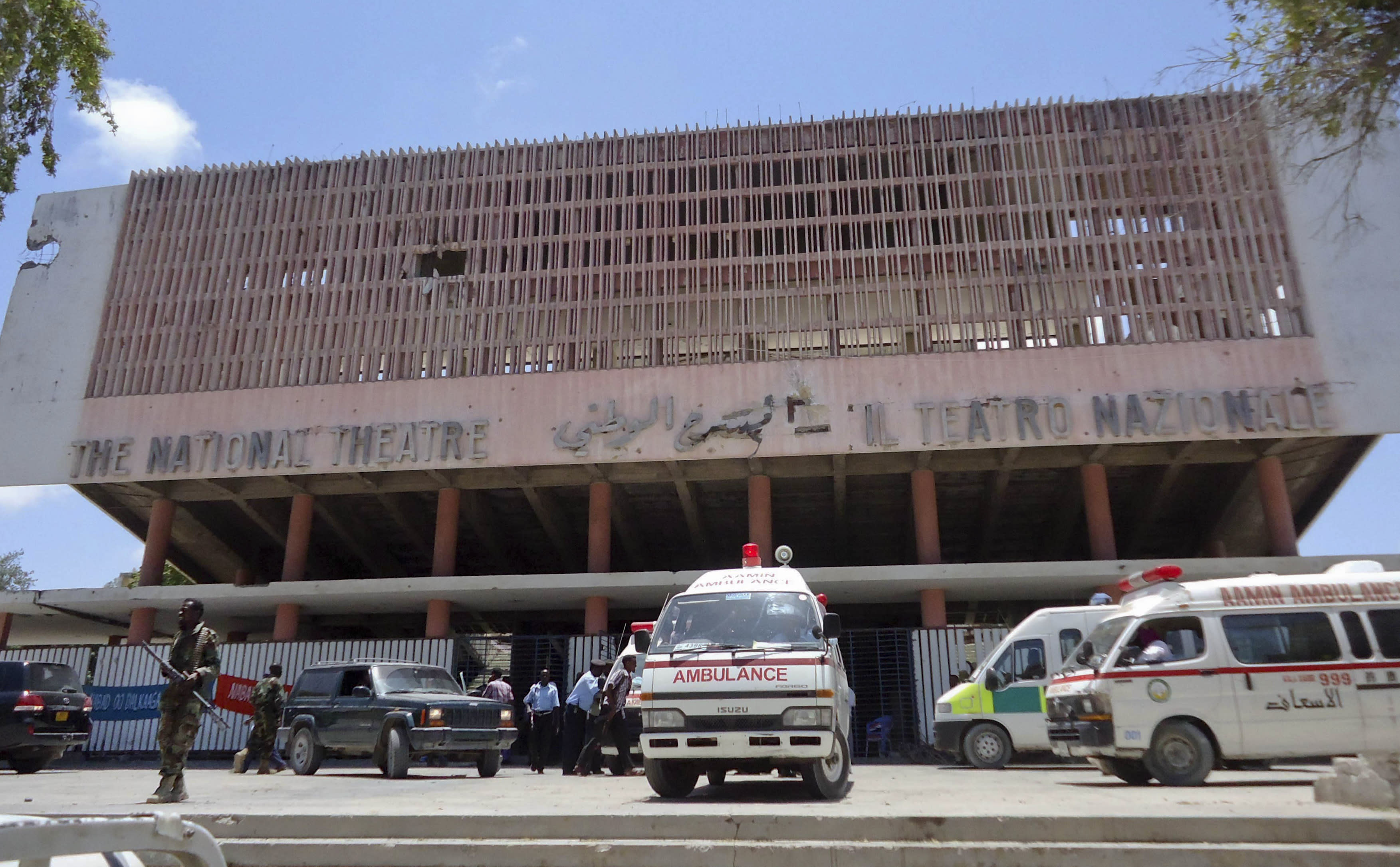 Ambulances stand outside the Somali National Theater in Mogadishu, Somalia Wednesday, April 4, 2012. An explosion Wednesday at a ceremony at Somalia's national theater killed at least 10 people including two top sports officials in an attack by an Islamist group on a site that symbolized the city's attempt to rise from two decades of war. (AP Photo/Farah Abdi Warsameh)
