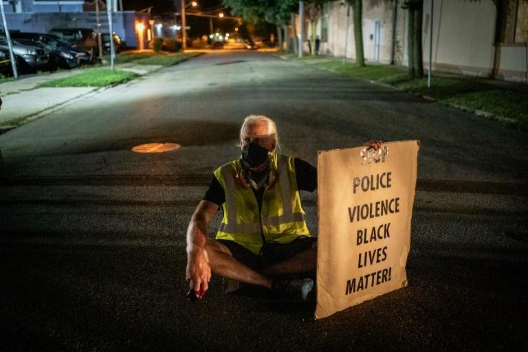 A protester sits in the street while holding a placard during a demonstration against the shooting of Jacob Blake