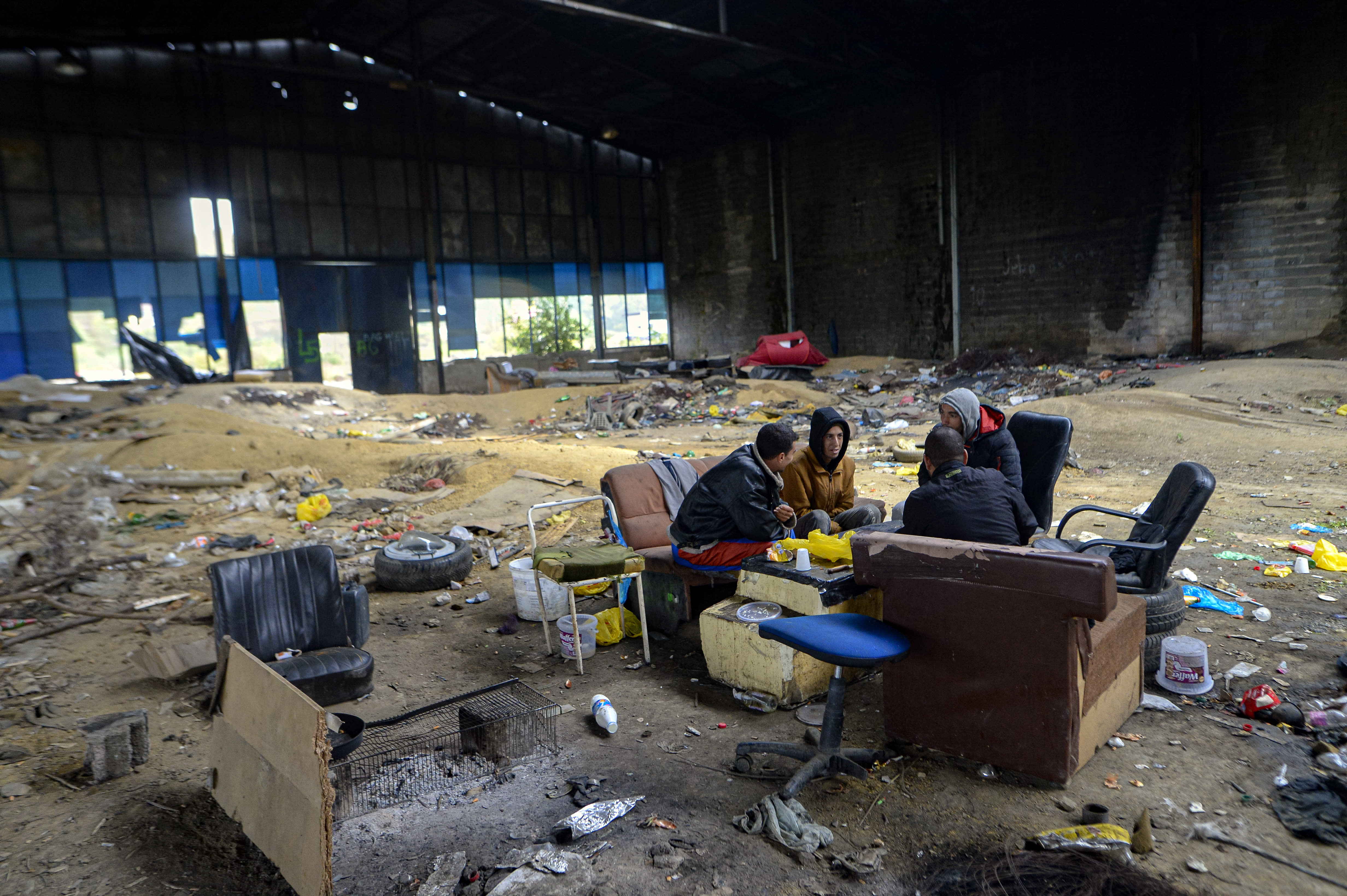 Migrants sit in an abandoned factory outside Velika Kladusa, Bosnia, Saturday, Sept. 26, 2020. Remote woods, abandoned run-down buildings and roadsides on the fringes of northwestern Bosnian towns are steadily filling with makeshift camps where migrants from the Middle East, Asia and North Africa are bracing for more misery as autumn's chill and rains set it. (AP Photo/Kemal Softic)