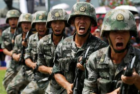 FILE PHOTO: People's Liberation Army (PLA) soldiers take part in a performance during an open day at Stonecutters Island naval base in Hong Kong