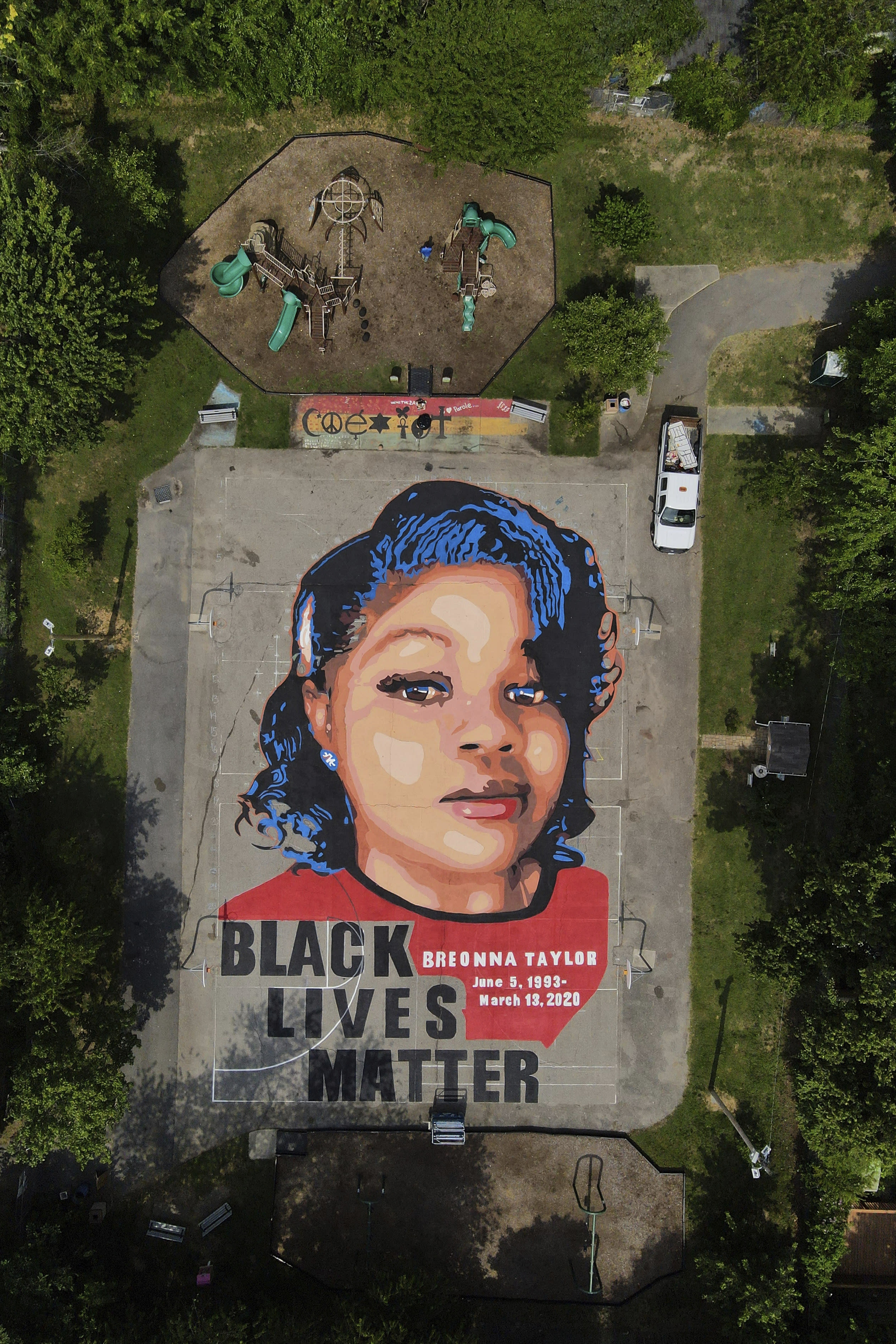 A ground mural depicting a portrait of Breonna Taylor is seen at Chambers Park, Monday, July 6, 2020, in Annapolis, Md. The mural honors Taylor, a 26-year old Black woman who was fatally shot by police in her Louisville, Ky., apartment. The artwork was a team effort by the Banneker-Douglass Museum, the Maryland Commission on African American History and Culture, and Future History Now, a youth organization that focuses on mural projects. (AP Photo/Julio Cortez)