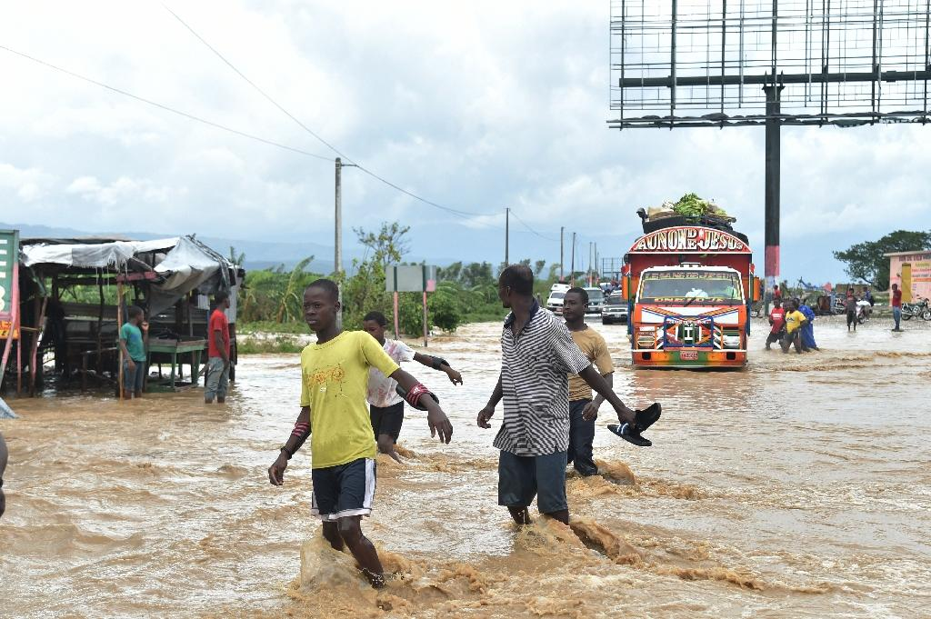 People try to cross the overflowing La Rouyonne river in the commune of Leogane, south of Port-au-Prince, October 5, 2016