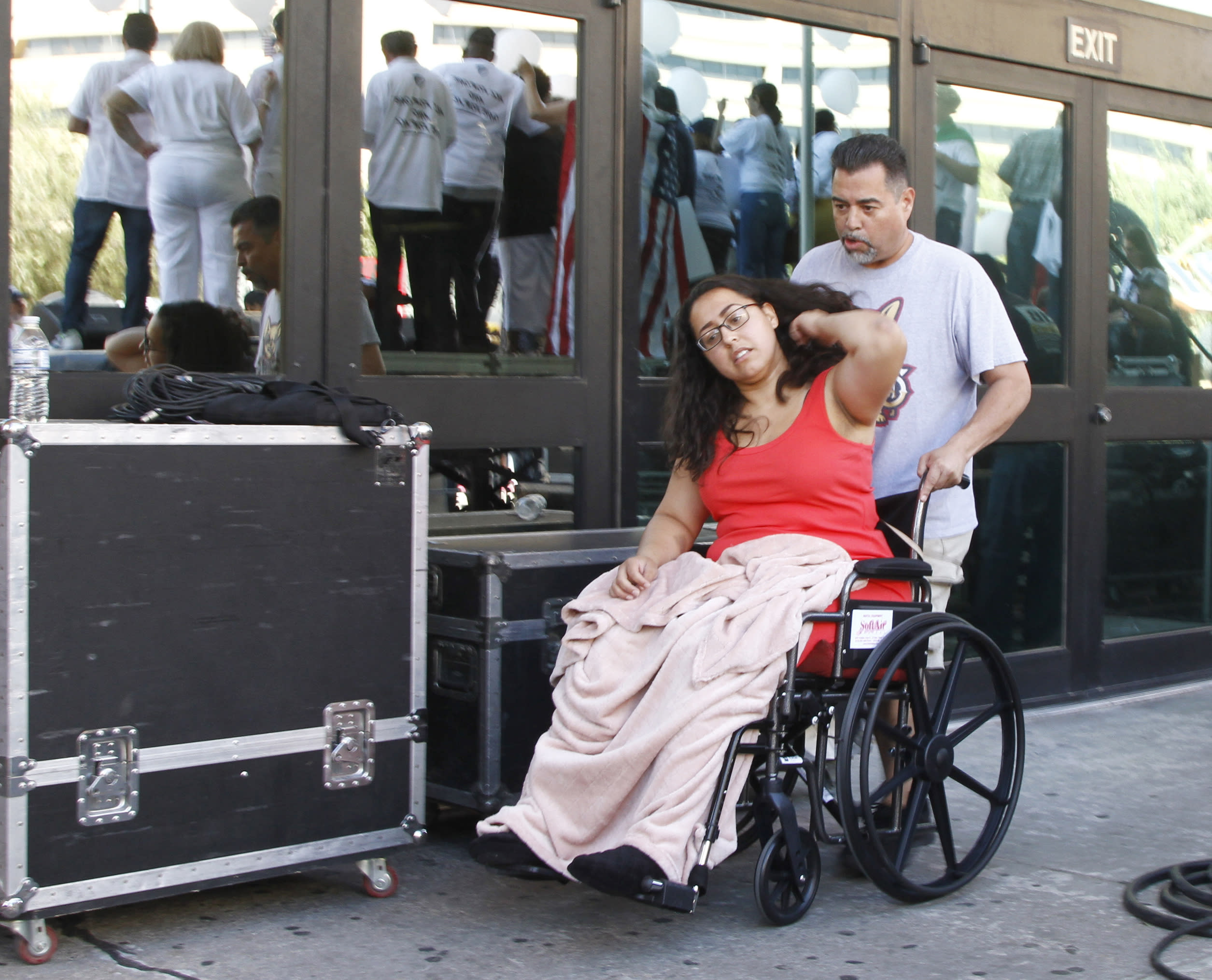 "CORRECTS TO AUG. 10, NOT 8 - Jessica Coca Garcia is wheeled away after speaking at League of United Latin American Citizens' ""March For a United America,"" in El Paso, Texas, on Saturday, Aug. 10, 2019, a week after she and her husband were injured by bullets during a mass shooting. More than 100 people marched through the Texas border denouncing racism and calling for stronger gun laws one week after several people were killed in a mass shooting that authorities say was carried out by a man targeting Mexicans. (AP Photo/Cedar Attanasio)"