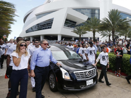 Miami Marlins owner and CEO Jeffrey Loria, second left, and Marlins president David Samson, right, lead players and staff as they escort a hearse carrying the body of pitcher Jose Fernandez as it leaves Marlins Park stadium, Wednesday, Sept. 28, 2016, in Miami. Fernandez was killed in a weekend boat crash along with two friends. (AP Photo/Wilfredo Lee)