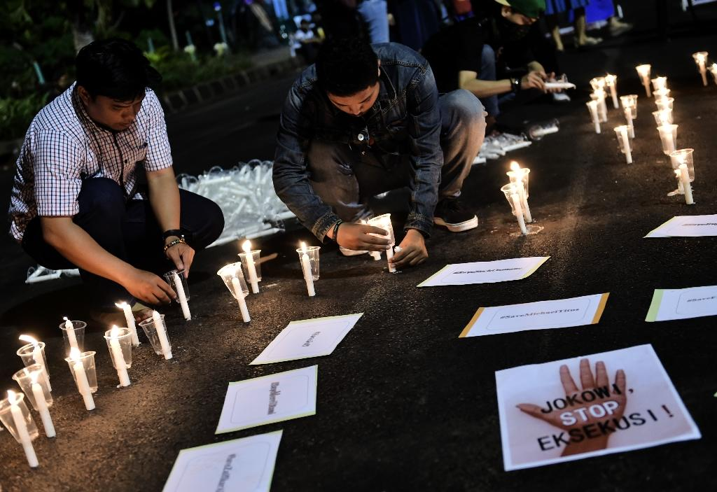 Indonesian men light candles during an anti-execution rally in front of the presidential palace in Jakarta on July 28, 2016 (AFP Photo/Bay Ismoyo)