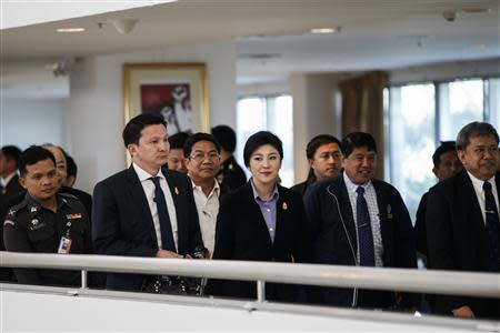 Thailand's Prime Minister Yingluck Shinawatra (C) leaves the Government Complex after a meeting with the Election Commission in Bangkok December 20, 2013. REUTERS/Athit Perawongmetha