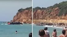 Stunned tourists watch as boatload of migrants land on busy beach