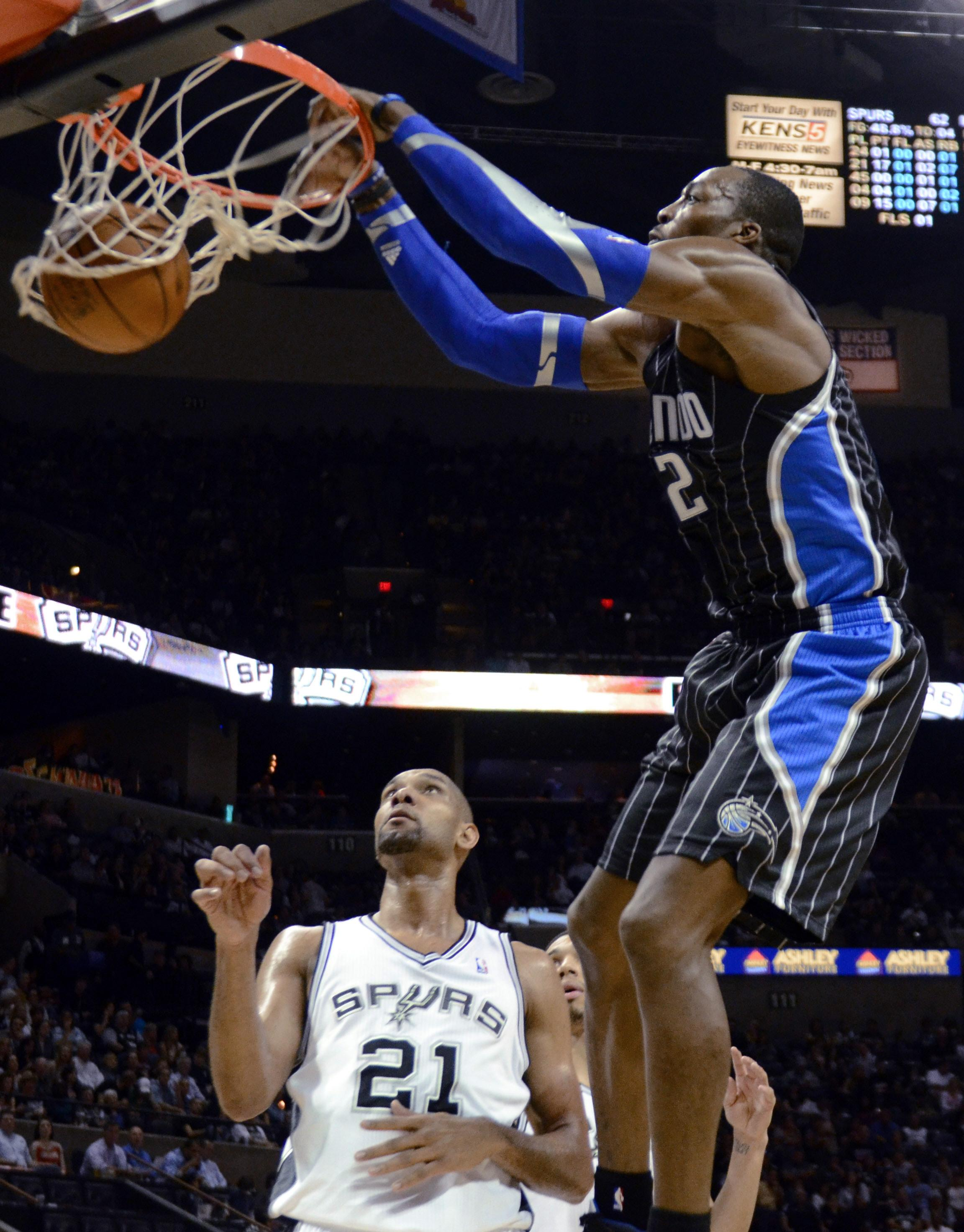 Orlando Magic center Dwight Howard scores on an dunk in front of San Antonio Spurs forward Tim Duncan during the second half of an NBA basketball game Wednesday, March 14, 2012, in San Antonio. (AP Photo/Bahram Mark Sobhani)