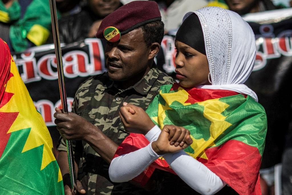 A demonstrator (L) joins members of the Oromo, Ogaden and Amhara community in South Africa as they demonstrate on August 18, 2016 in Johannesburg against the crackdown in the restive Oromo and Amhara region of Ethiopia (AFP Photo/Gulshan Khan)