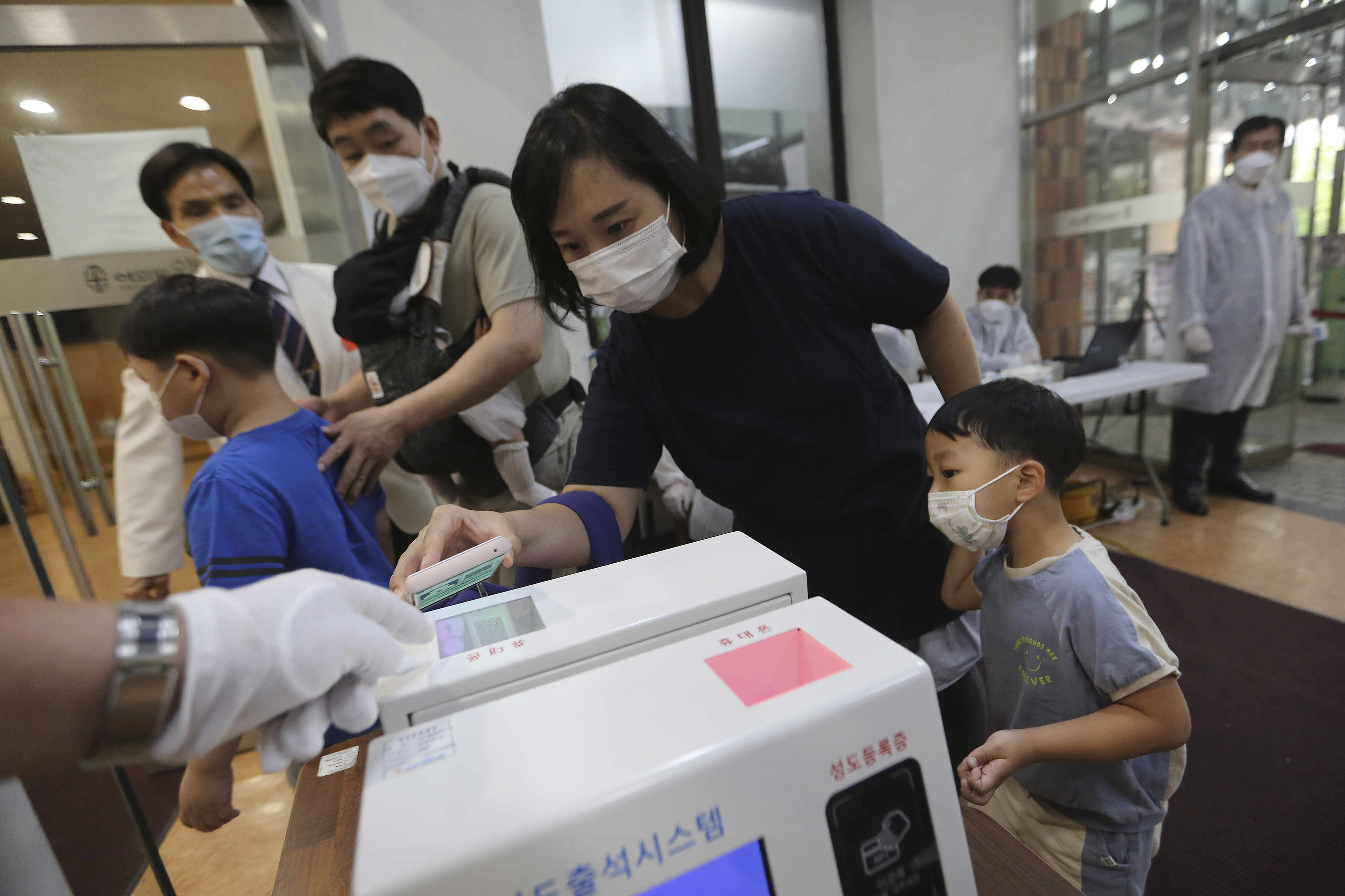 A Christian woman wearing a face mask to help protect against the spread of the new coronavirus scans a QR code on her smartphone before attending a service at the Yoido Full Gospel Church in Seoul, South Korea, Sunday, July 5, 2020. (AP Photo/Ahn Young-joon)