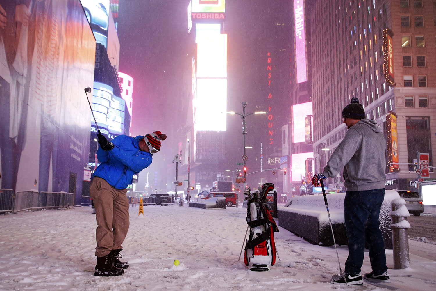 <p>Two men play golf with a tennis ball as a snowstorm sweeps through Times Square, Tuesday, March 14, 2017, in New York. (Mark Lennihan/AP) </p>