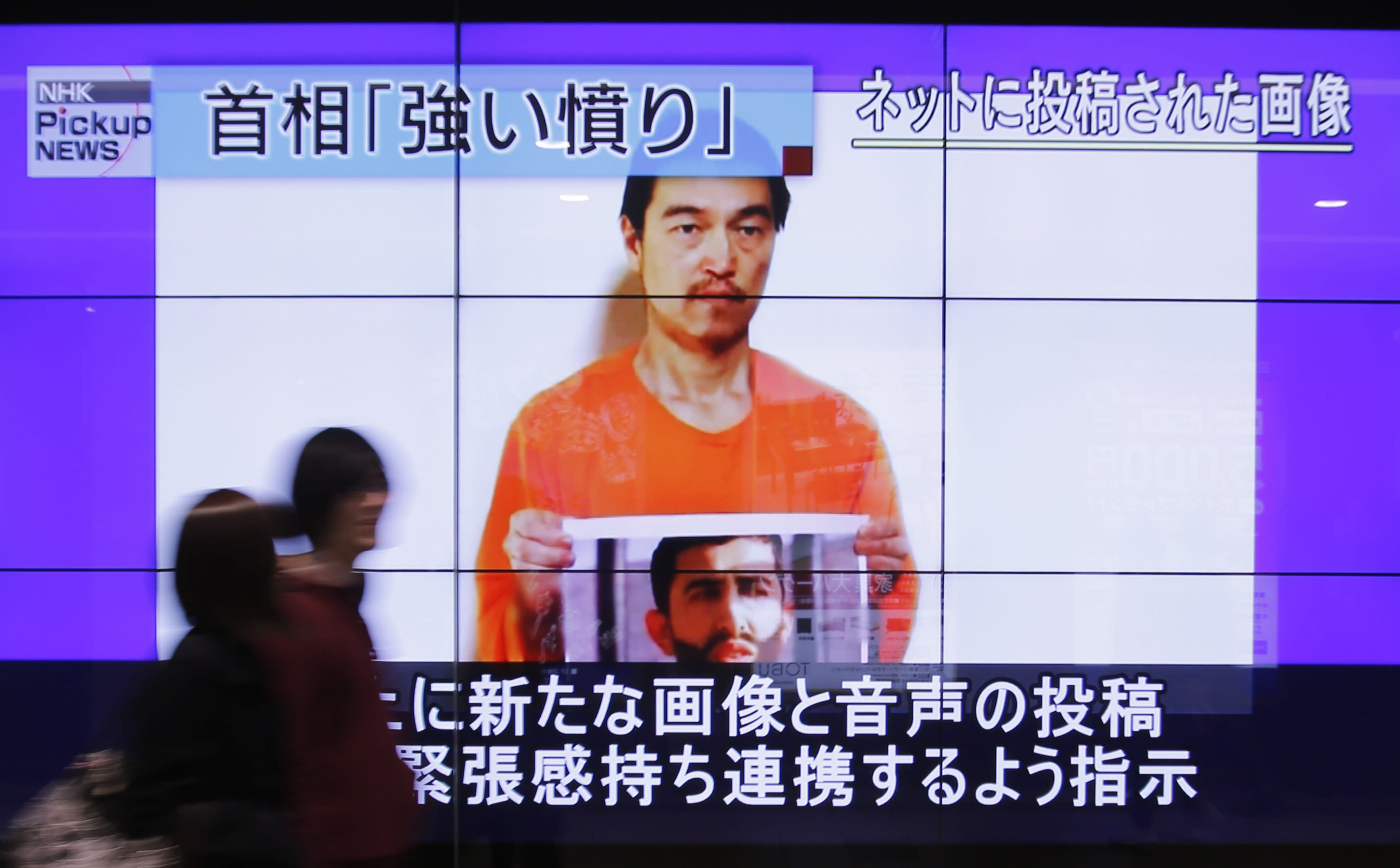 People walk past television screens displaying a news program, about an Islamic State video showing Japanese captive Kenji Goto, on a street in Tokyo January 28, 2015. Jordan said on Wednesday it was willing to hand over an Iraqi woman jailed for her role in a 2005 suicide bomb attack if a Jordanian pilot captured by Islamic State was released. Government spokesman Mohammad al-Momani made no mention of Japanese hostage Kenji Goto, a veteran war reporter who is also being held by the militant group. REUTERS/Yuya Shino (JAPAN - Tags: POLITICS CIVIL UNREST)