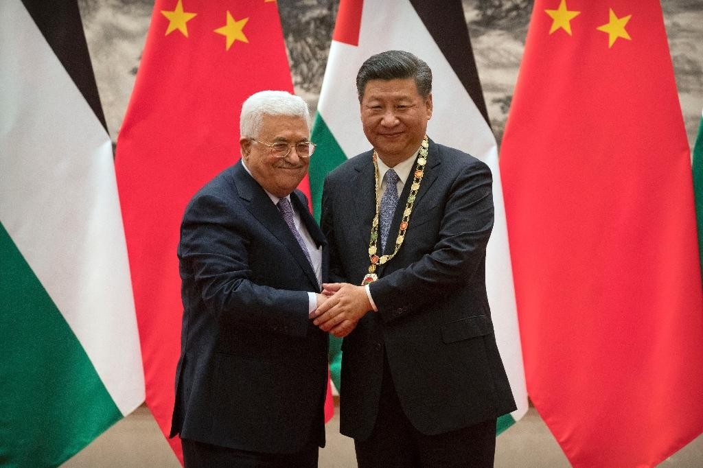Palestinian President Mahmoud Abbas (left) shakes hands after presenting a medallion to Chinese President Xi Jinping during a signing ceremony at the Great Hall of the People in Beijing on July 18, 2017