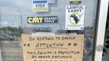 Sign at Michigan shop warns masked customers of armed employees. 'Lighten up,' owner says.