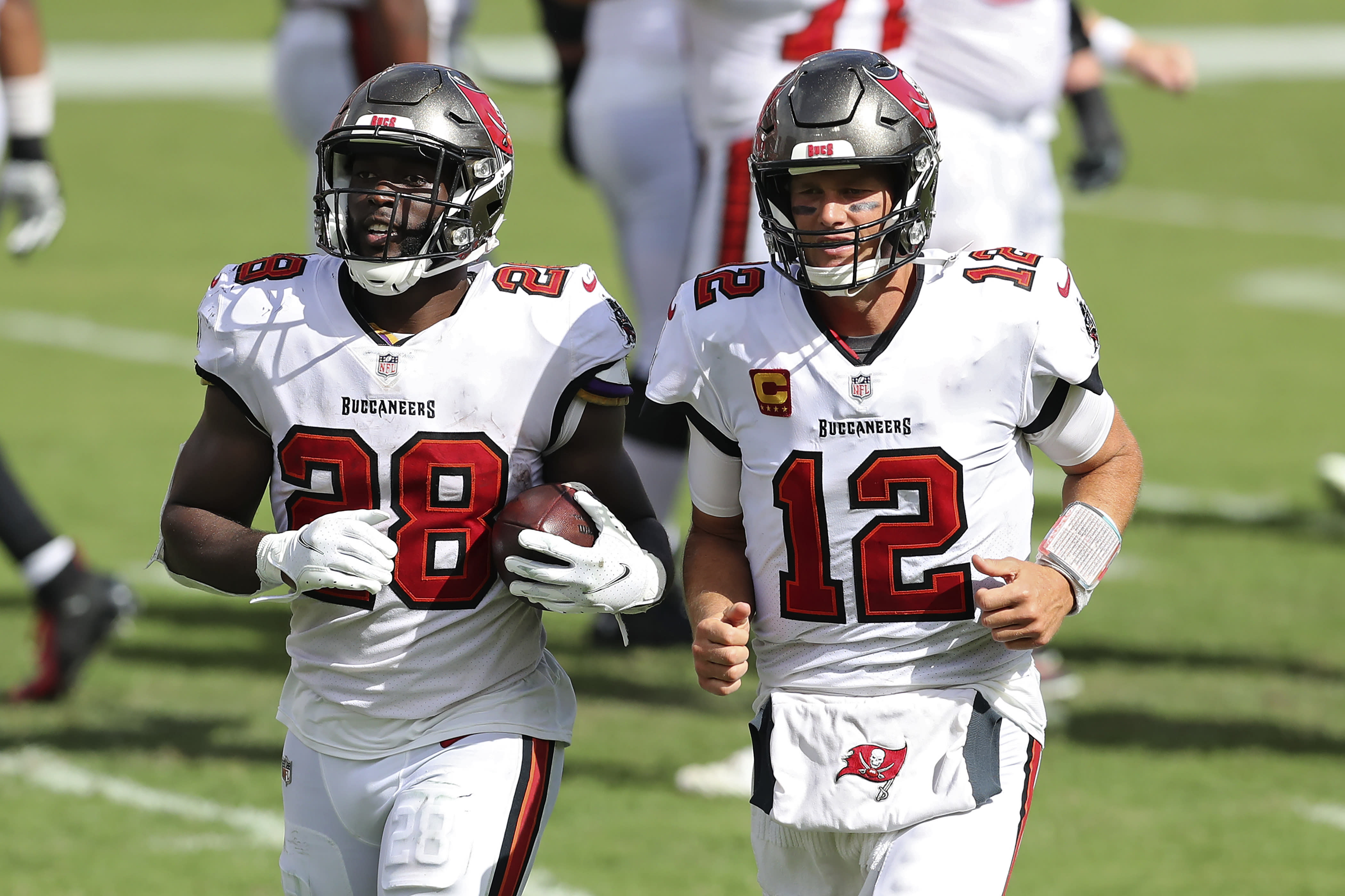 Tampa Bay Buccaneers running back Leonard Fournette (28) runs off the field with quarterback Tom Brady (12) after Fournette ran 46-yards for a score against the Carolina Panthers during the second half of an NFL football game Sunday, Sept. 20, 2020, in Tampa, Fla. (AP Photo/Mark LoMoglio)