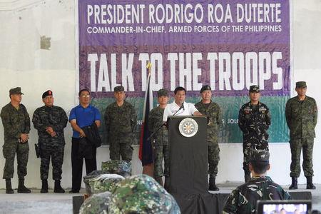Philippines' President Rodrigo Duterte (C), flanked by military and police officials, talks to troopers during his visit to Camp Teodulfo Bautista in Jolo, Sulu, Philippines