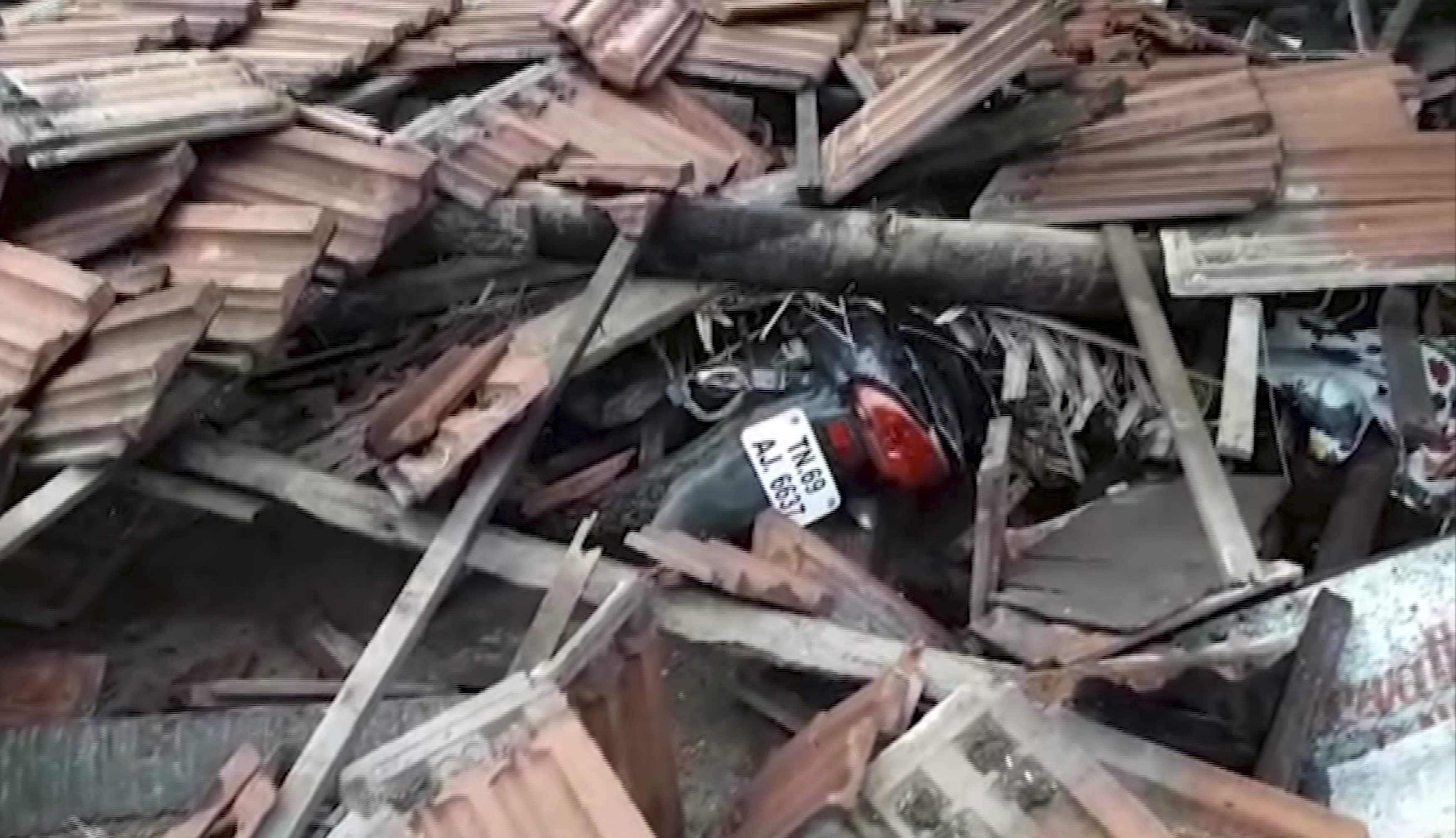 In this grab made from video provided by KK Productions, a motorcycle is covered in debris from a house that collapsed when a cyclone struck Nagapattinam, in the southern Indian state of Tamil Nadu, Friday, Nov. 16, 2018. Cyclone Gaja hit the coast of southern India on Friday, killing more than 10 people and damaging homes after more than 80,000 residents were evacuated. (KK Production via AP)