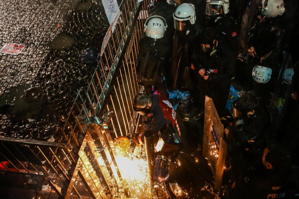Turkish anti riot police officers try to open a chained gate at the Turkish Zaman Daily newspaper headquarters on March 4, 2016 in Istanbul (AFP Photo/Ozan Kose)