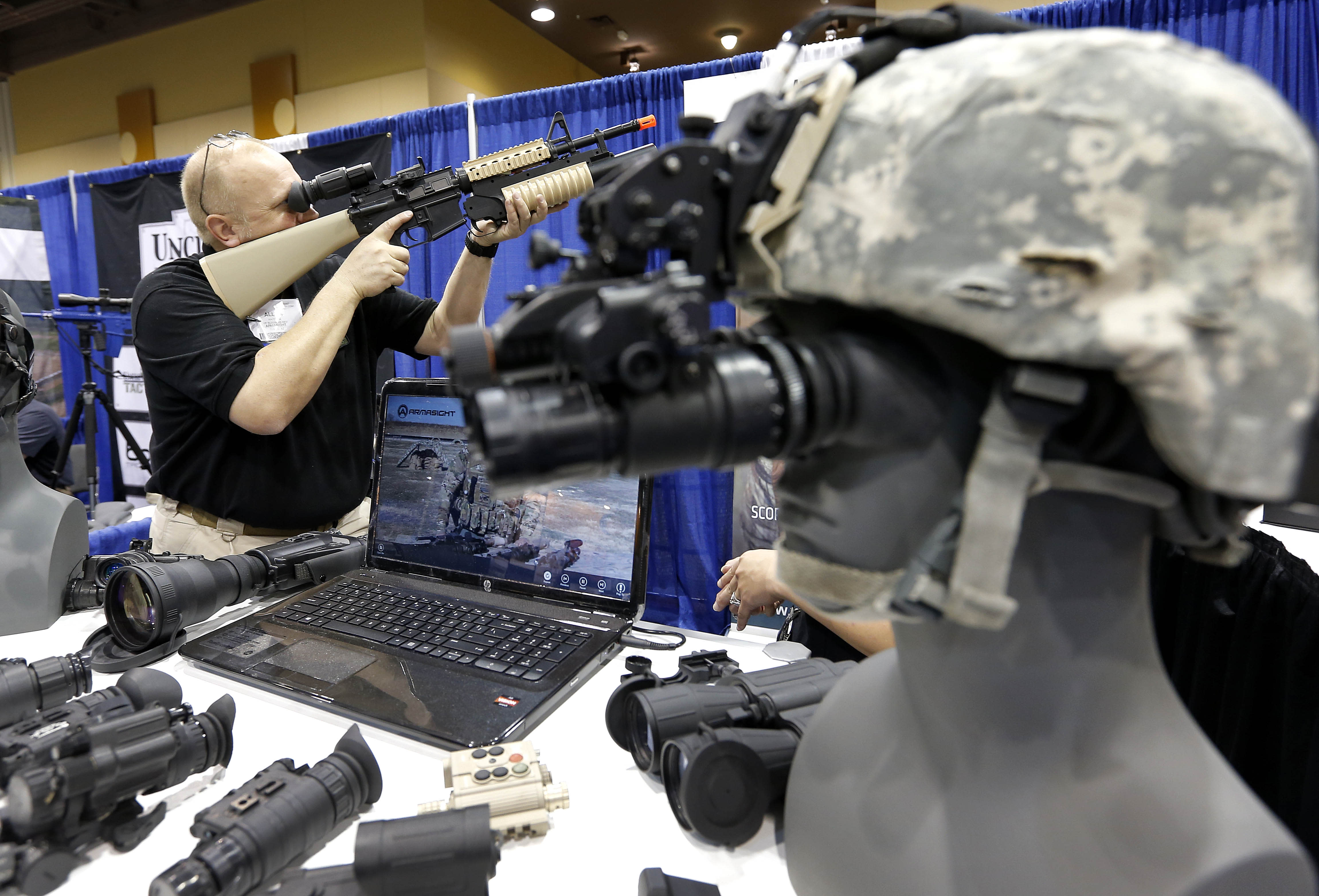 Allen Harding, of Armasight, demonstrates his products Tuesday, March 12, 2013 at the Border Security Expo in Phoenix. More than 180 companies are exhibiting their security products despite automatic spending cuts that are affecting every federal government agency due to the government sequestration. (AP Photo/Matt York)