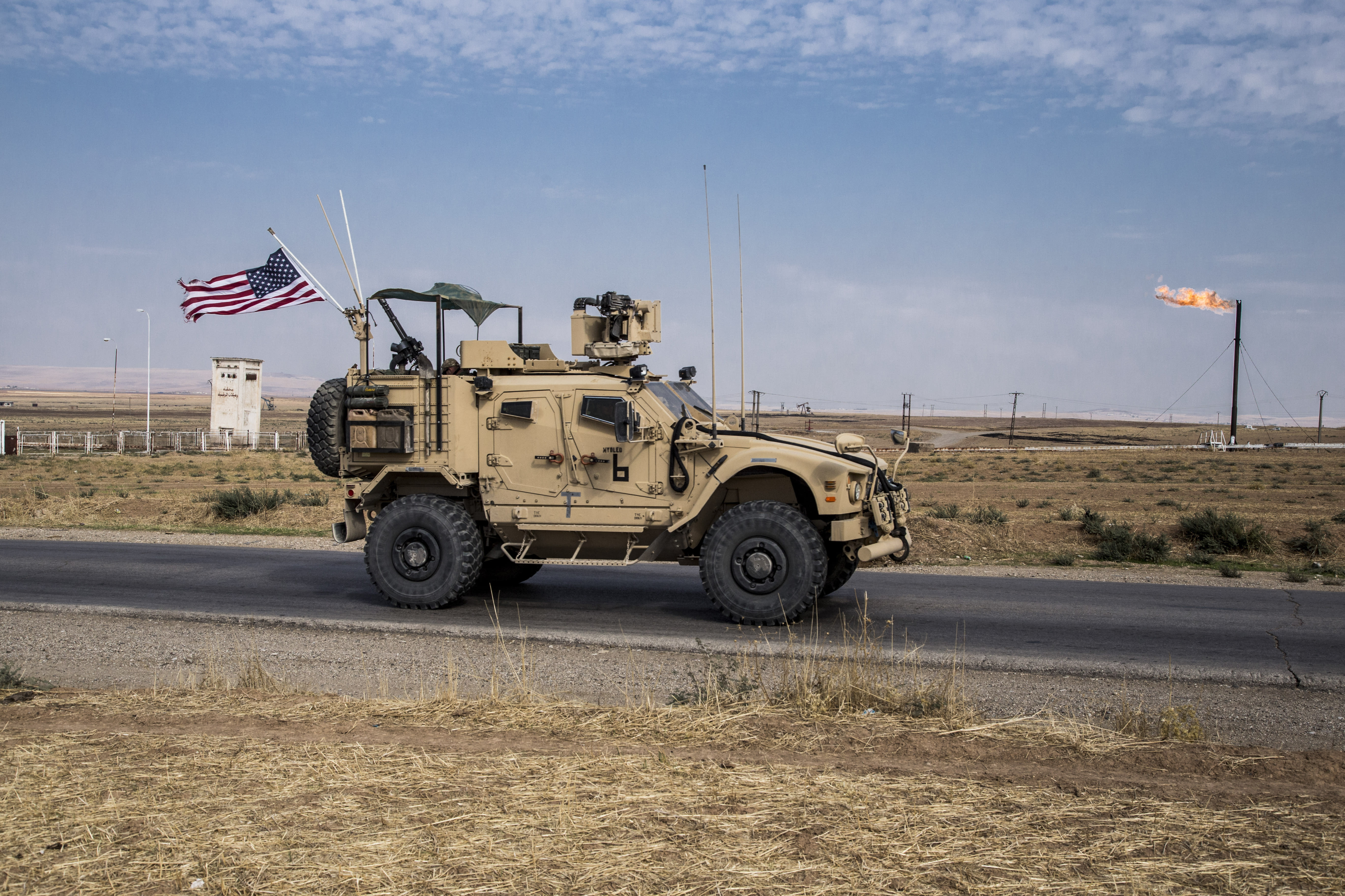 FILE - In this Monday, Oct. 28, 2019 file photo, U.S. forces patrol Syrian oil fields, in eastern Syria.President Donald Trump's decision to dispatch new U.S. forces to eastern Syria to secure oil fields is being criticized by some experts as ill-defined and ambiguous. But the residents of the area, one of the country's most remote and richest regions, hope the U.S. focus on eastern Syria would bring an economic boon and eliminate what remains of the Islamic State group. (AP Photo/Baderkhan Ahmad, File)