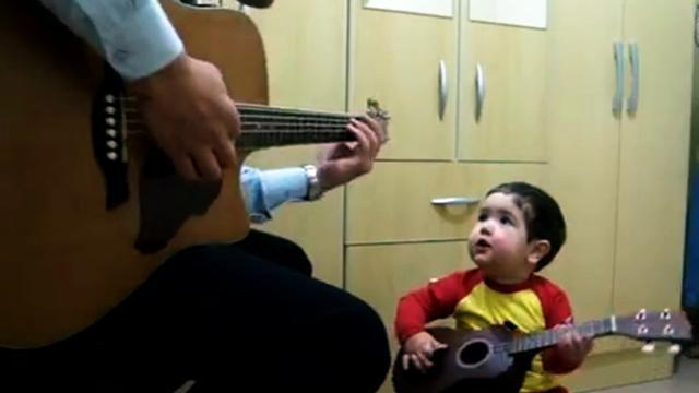 Adorable father and son sing The Beatles