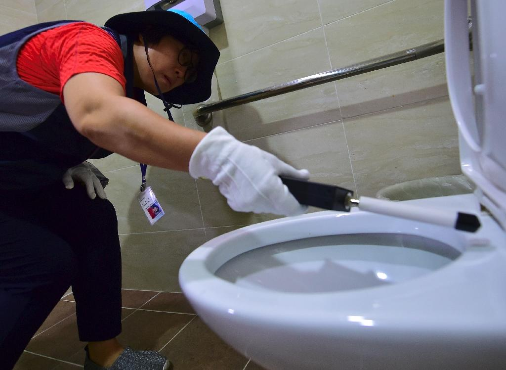 A member of Seoul's 'hidden camera-hunting' squad moves a hand-held detector around the toilet seat of a women's bathroom stall in search of a 'secret camera' (AFP Photo/Jung Yeon-Je)