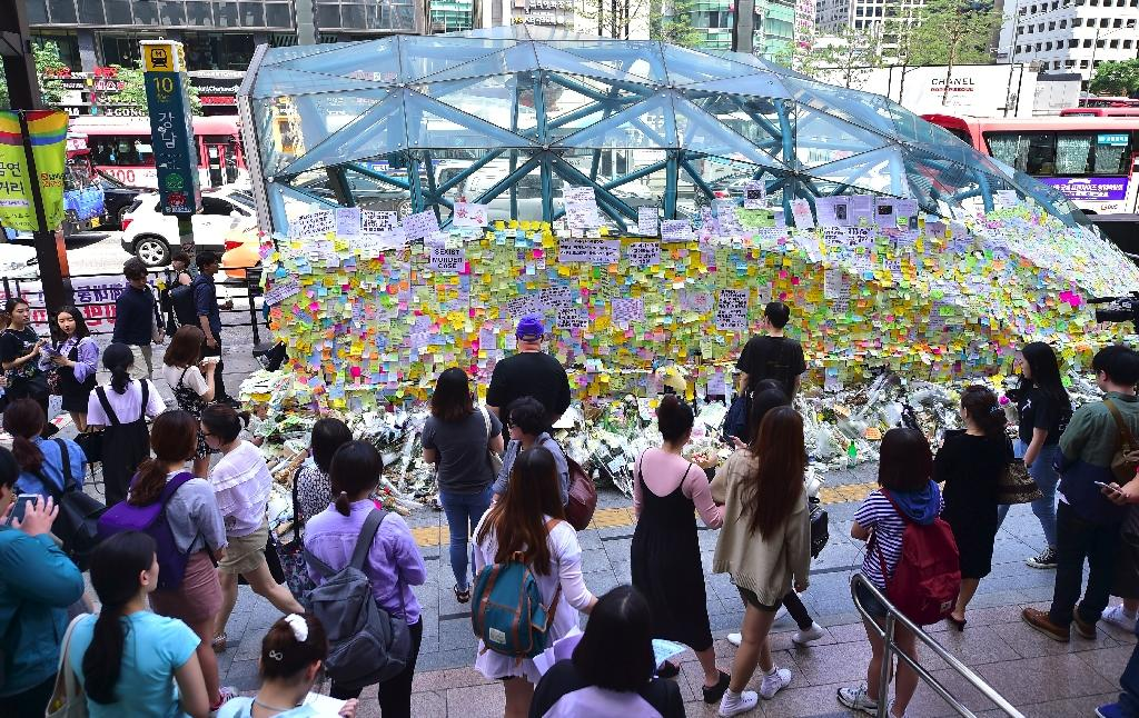 A subway station exit near the scene of the stabbing was turned into a shrine by South Koreans leaving flowers and covering its walls with post-it notes (AFP Photo/Jung Yeon-Je)