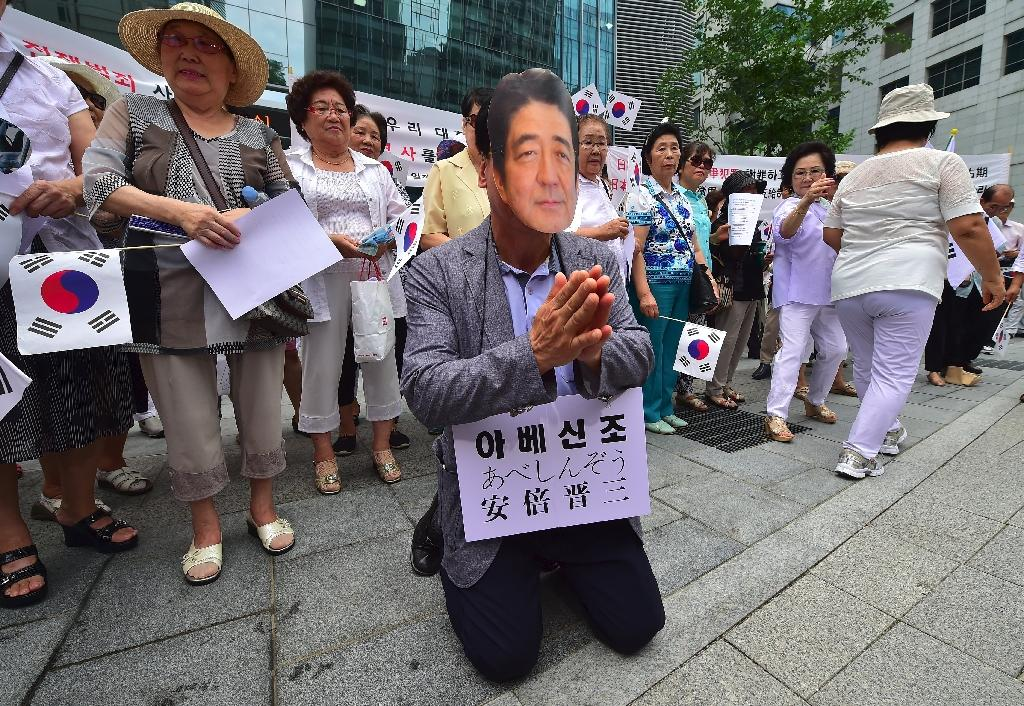 A man wearing a mask of Japanese Prime Minister Shinzo Abe kneels down in a mock apology during an anti-Japan rally to mark the 71st anniversary of South Korea's liberation from Japanese colonial rule, in Seoul, on August 15, 2016 (AFP Photo/Jung Yeon-Je)