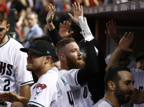 Diamondbacks pitcher Archie Bradley (center) shocked the Rockies with a two-run triple. (AP)